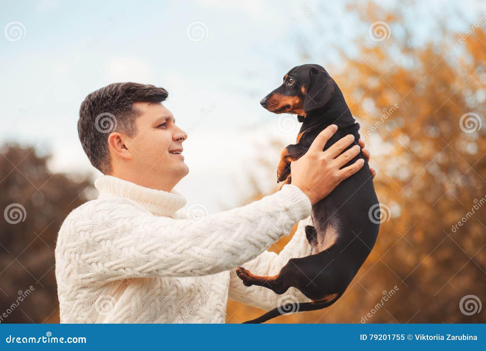 El perro lindo y su hombre hermoso joven del dueño se divierten en el parque, animales de los conceptos, animales domésticos