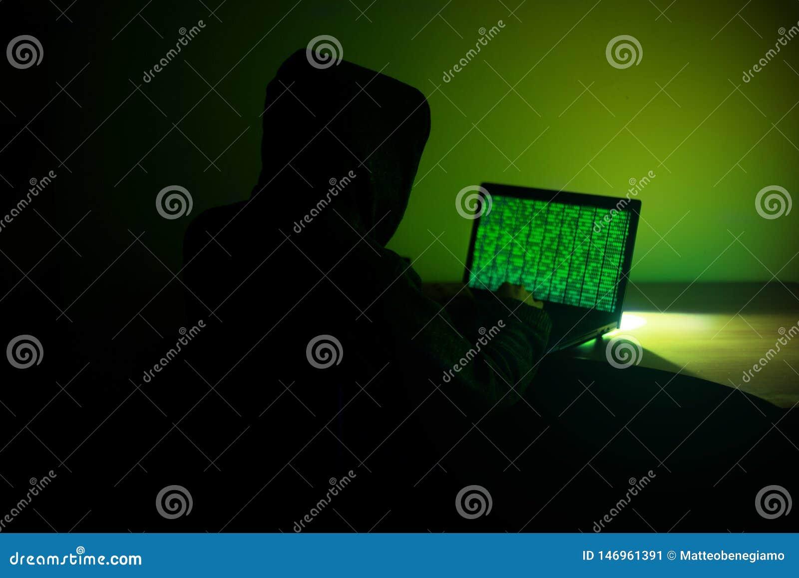 El pirata informático encapuchado está utilizando su ordenador para cortar el servidor