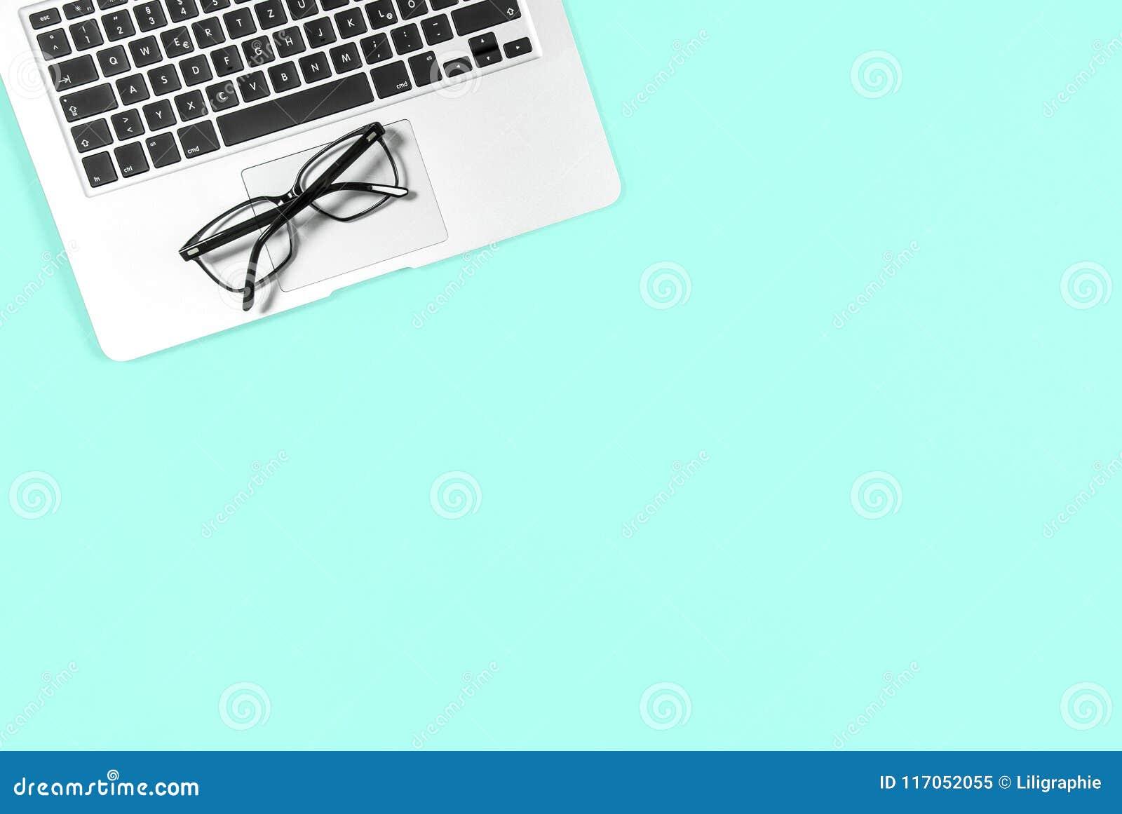 El plano mínimo del lugar de trabajo de la oficina pone los vidrios del ordenador portátil de la maqueta azules