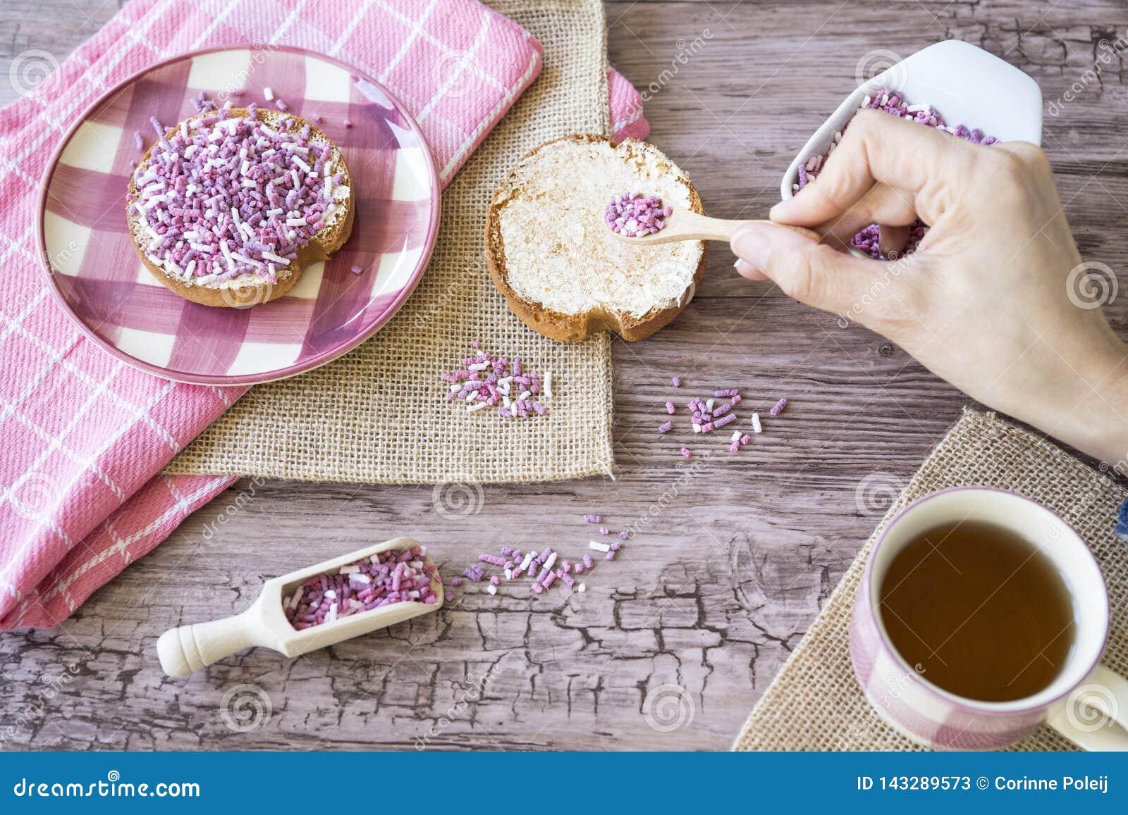El plano pone con el bizcocho tostado, la púrpura rosada dulce asperja y taza de té Contra fondo de madera