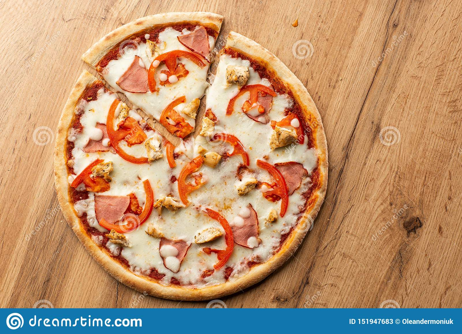 El plano pone con la pizza italiana tradicional con el pollo, el jamón, el queso y tomates en la parte posterior de madera
