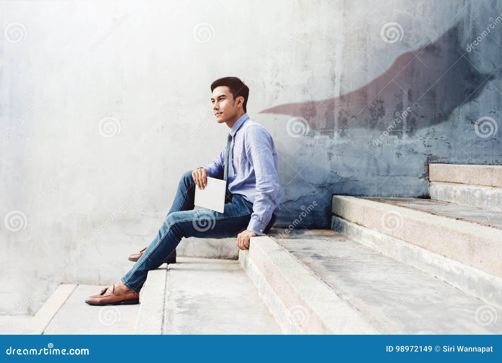 El poder, el éxito y la dirección en concepto del negocio, hombre joven se sientan