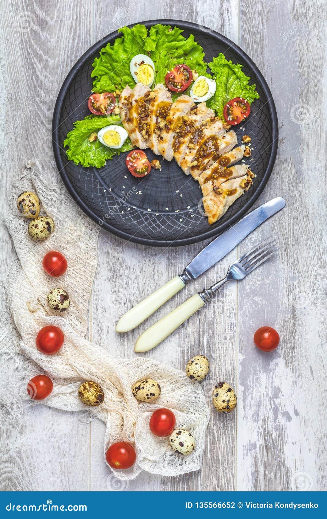 El pollo con la miel y la mostaza escabechan, lechuga, huevos de codornices, tomates de cereza