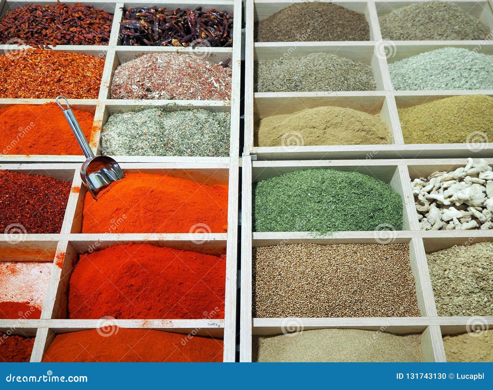 El polvo condimenta el surtido colorido en cajas de madera en un soporte del estante del mercado