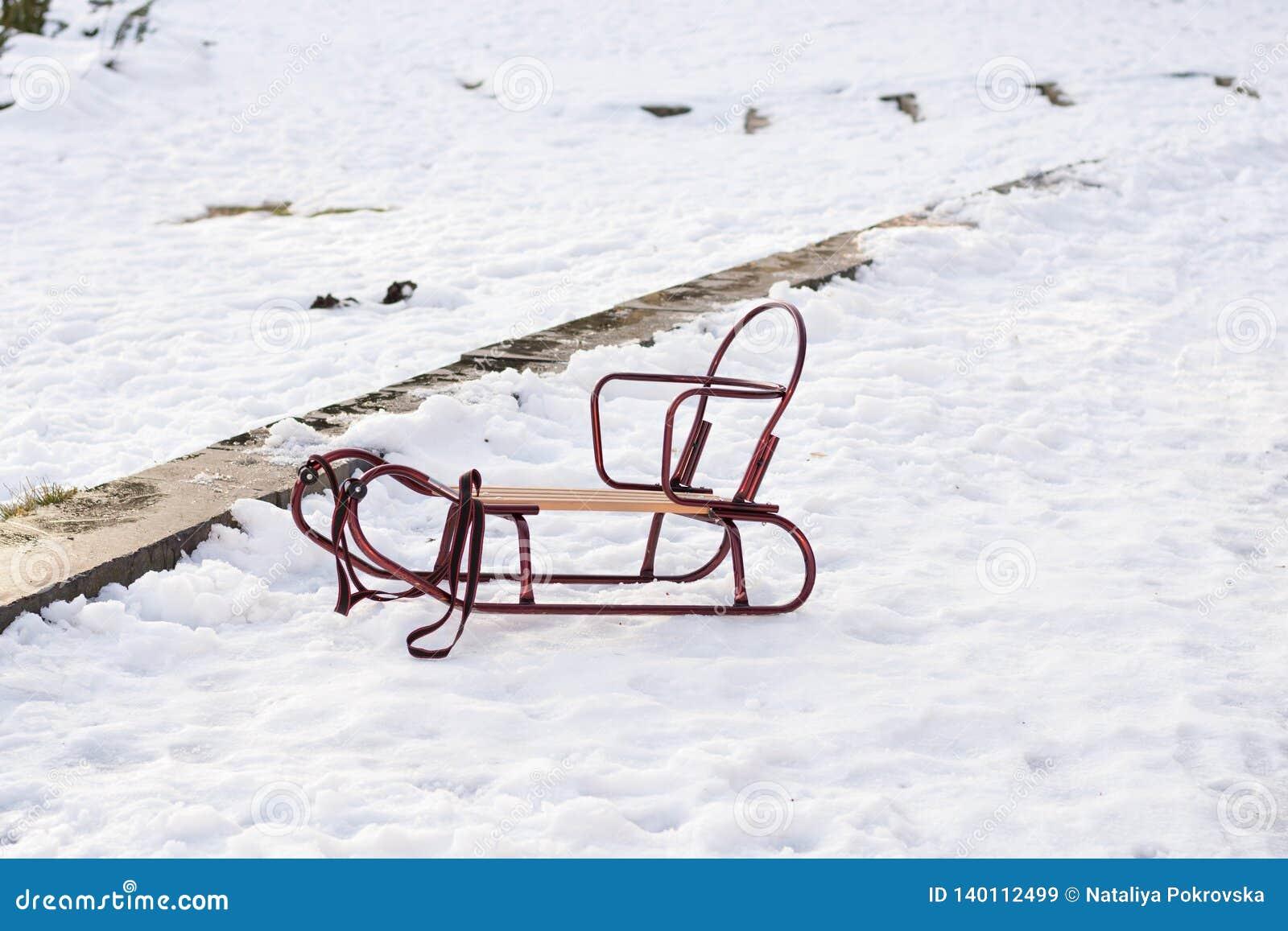 El práctico de costa vacío de los niños se está colocando en nieve en parque en día soleado del invierno Tiempo por diversión y f