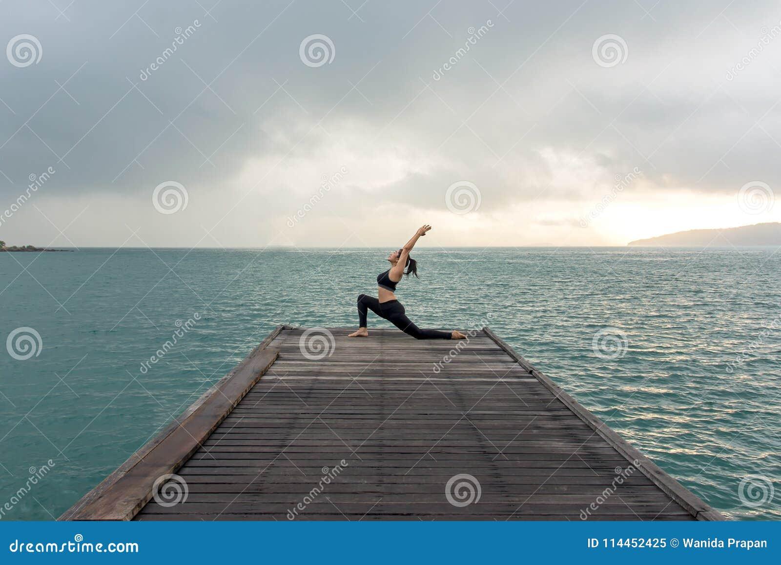 El practicar equilibrado forma de vida sana de la yoga de la mujer medita y energía en el puente por mañana
