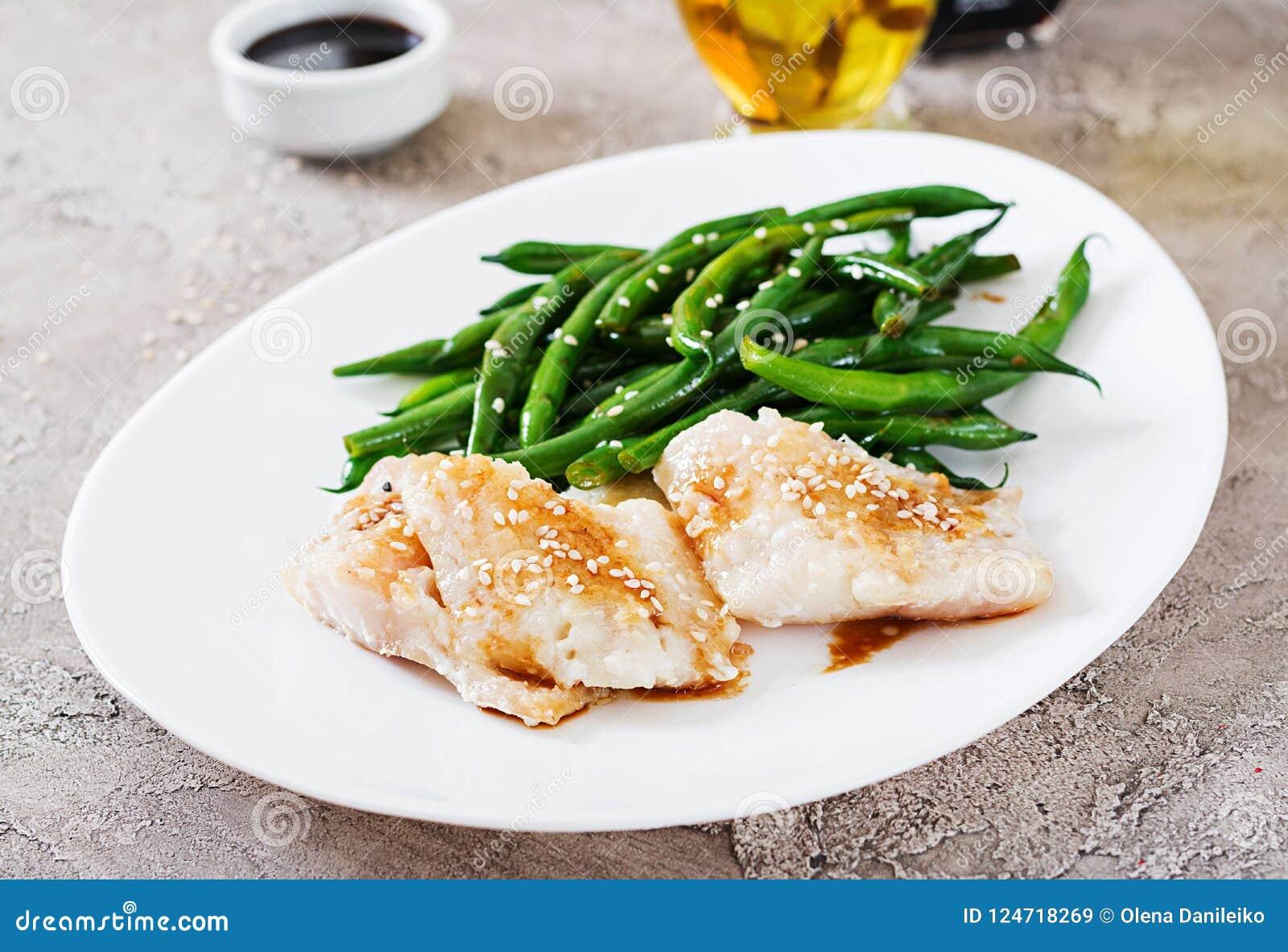 El prendedero de pescados sirvió con la salsa de soja y las habas verdes en la placa blanca