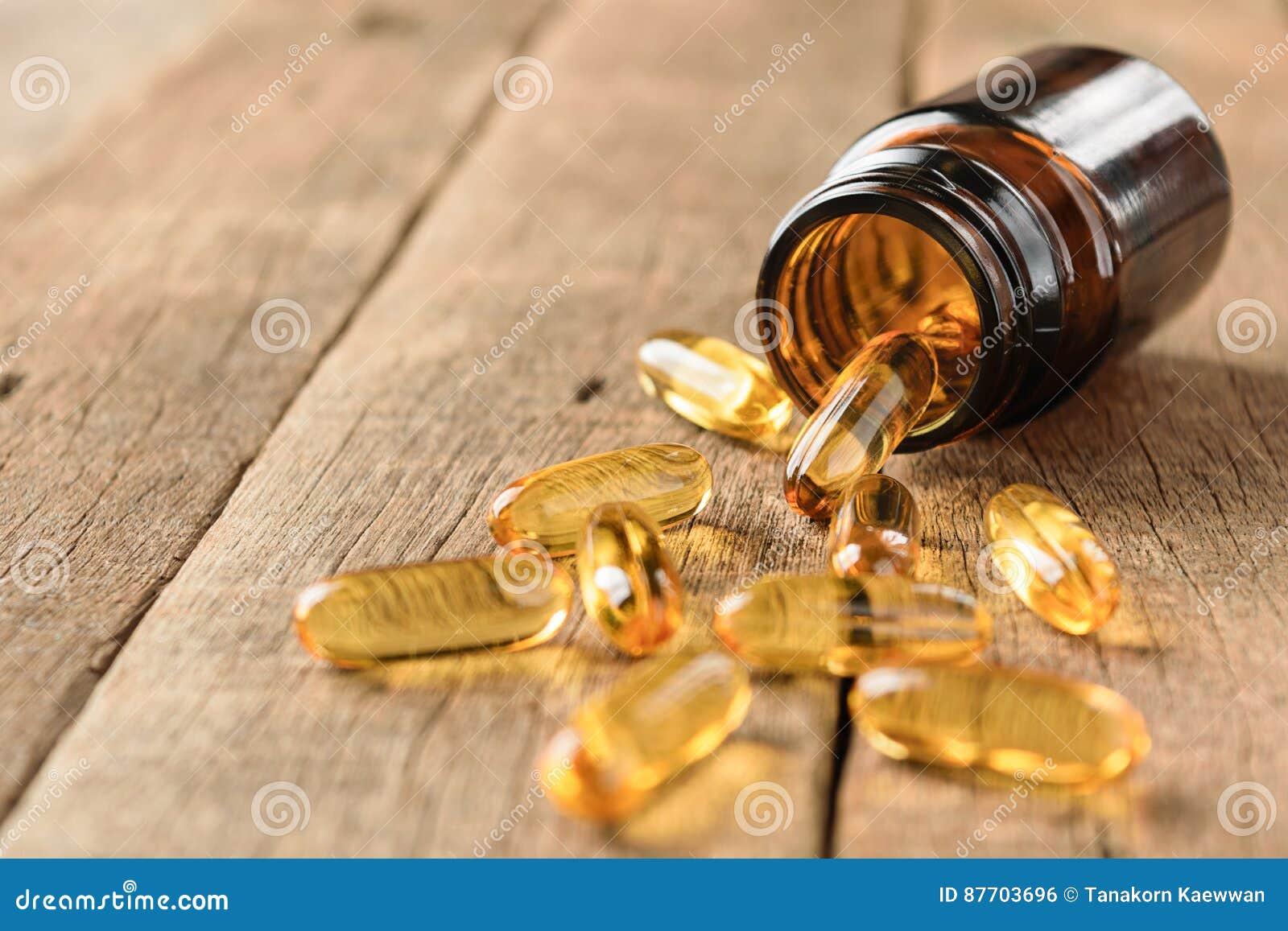 El primer complementa la botella de las vitaminas en el fondo de madera