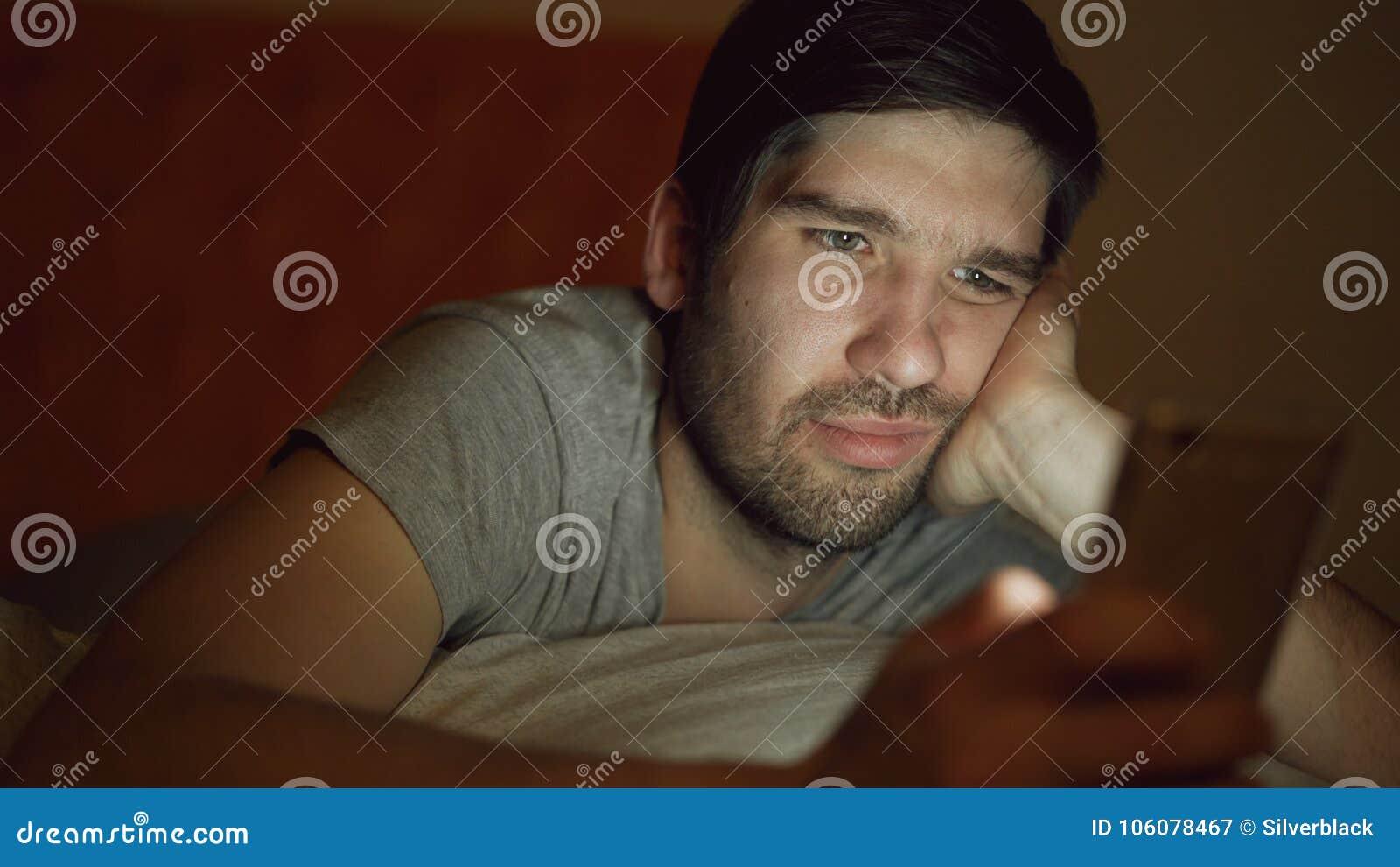 El primer de jóvenes aburrió al hombre que tenía el apego e insomnio de Internet usando el smartphone que mentía en cama en casa