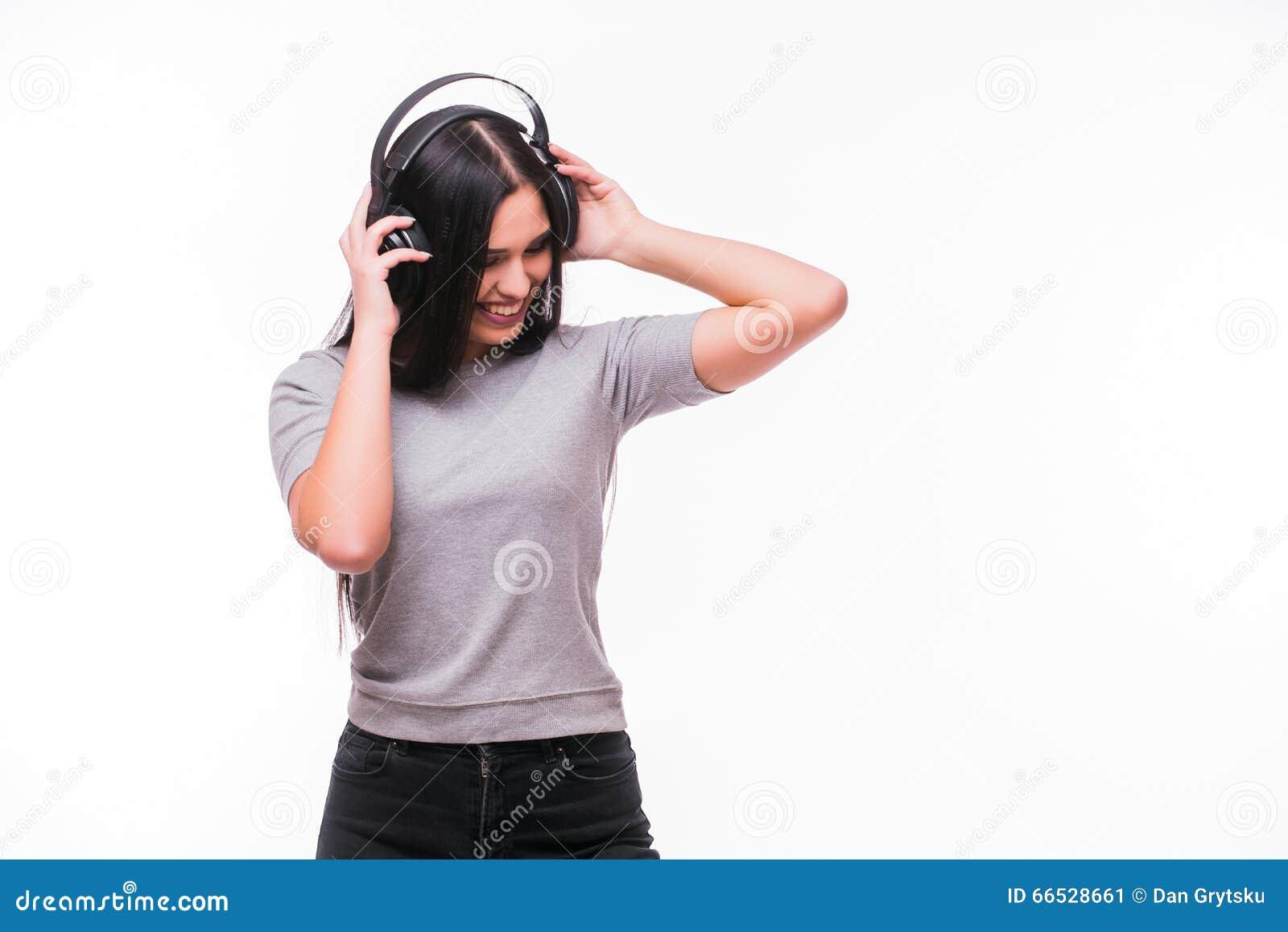 El primer de la muchacha caucásica morena feliz escucha baile la música con los auriculares