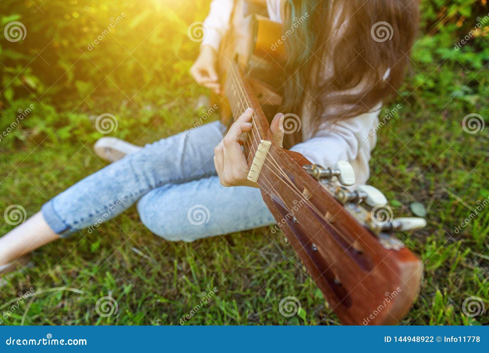 El primer de la mujer da tocar la guitarra ac?stica en fondo del parque o del jard?n Muchacha adolescente que aprende jugar la ca