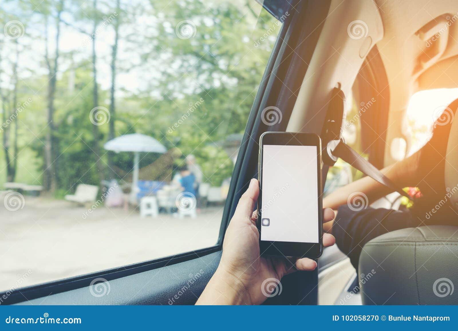 El primer del ` s del hombre da sostener smartphone en el interior del coche,