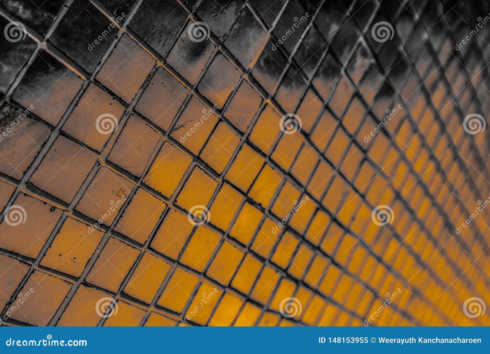El primer hermoso texturiza las tejas abstractas y el fondo negro de la pared del modelo del oro y amarillo del color y el papel