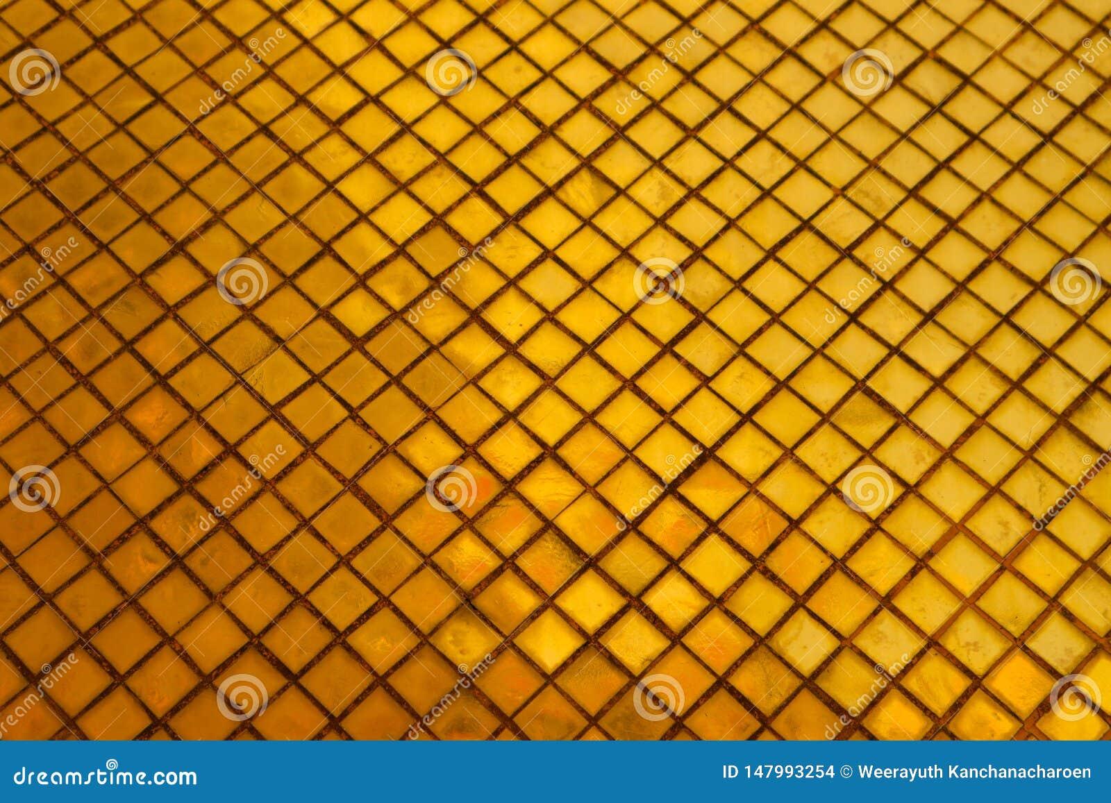 El primer hermoso texturiza las tejas y el fondo de la pared de vidrio del color oro y el papel pintado abstractos del arte