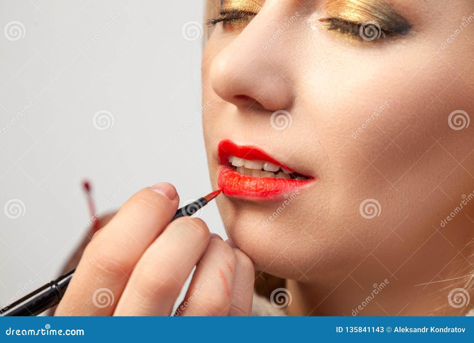 El primer que se aplica en los labios, el artista de maquillaje sostiene un cepillo en su mano y aplica la barra de labios roja e