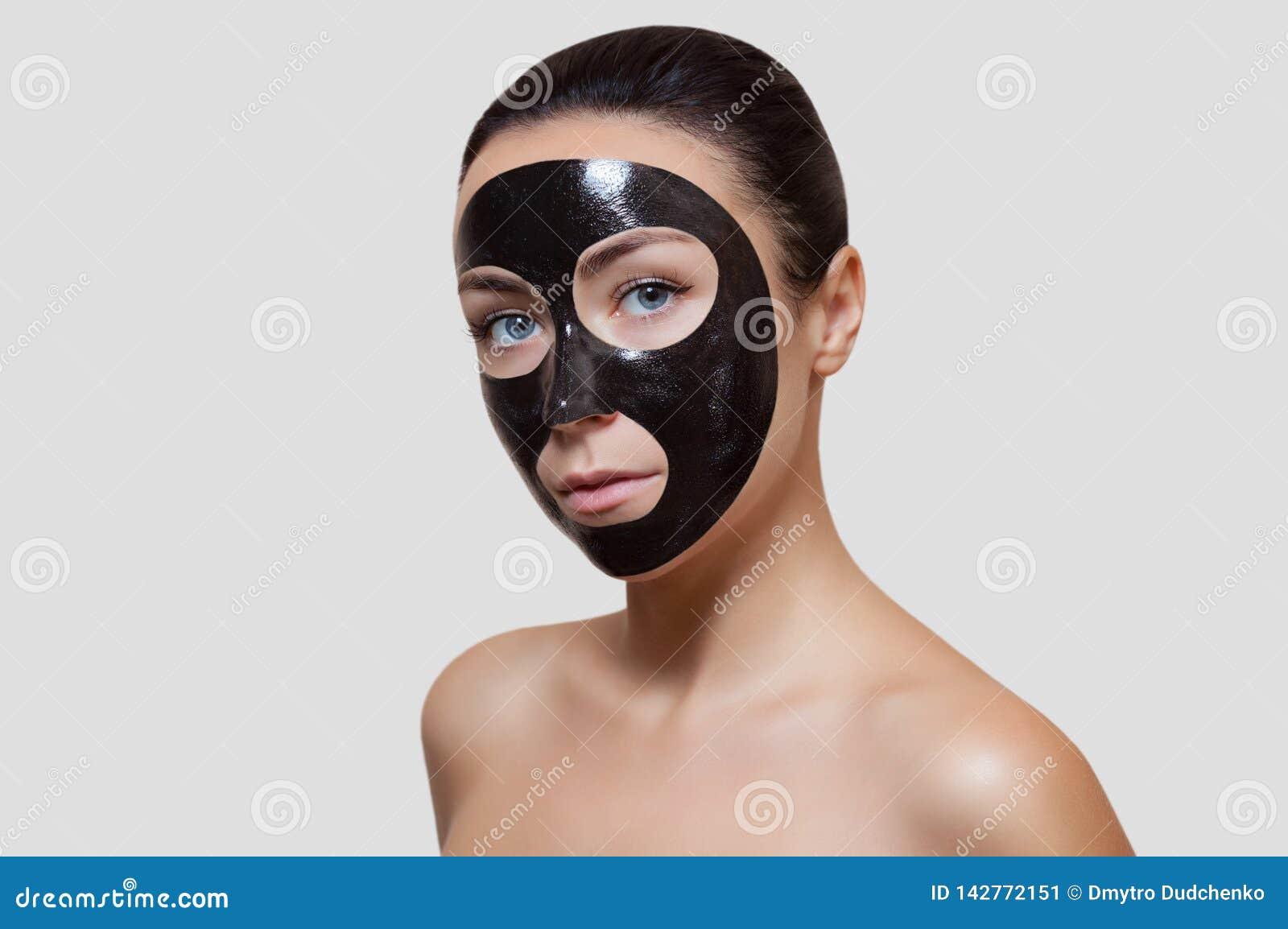El procedimiento para aplicar una máscara negra a la cara de una mujer hermosa