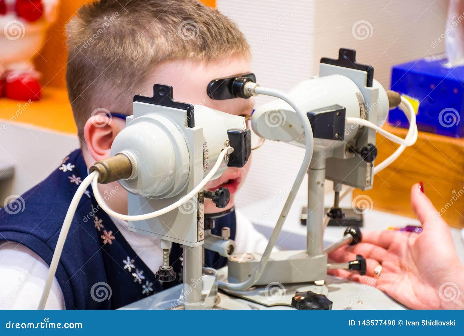 El procedimiento para los ojos del tratamiento del examen y del hardware de un niño El niño se sienta delante del tratamiento oft