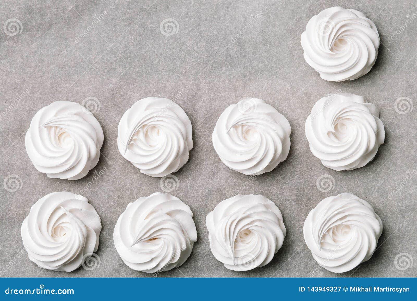 El proceso de hacer la melcocha Ciérrese encima de las manos del cocinero con crema del bolso de la confitería al papel de pergam