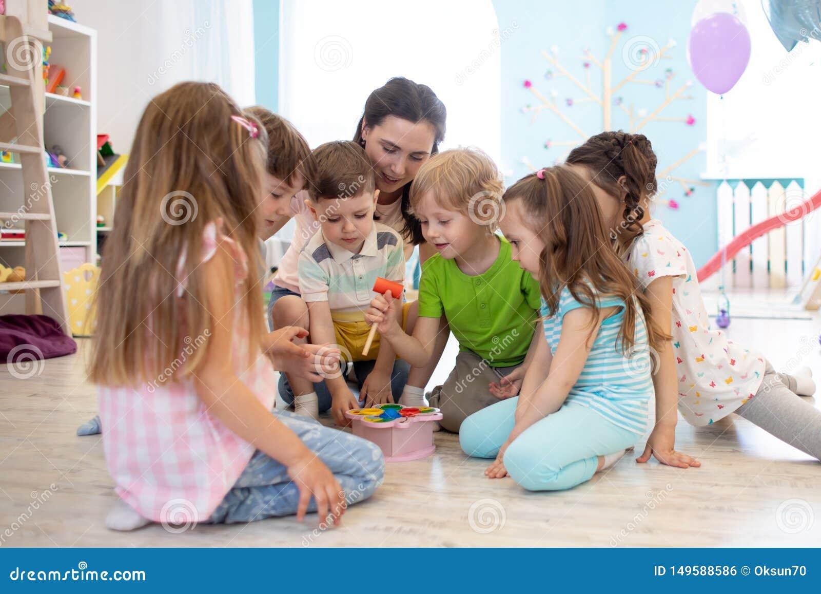 El profesor preescolar juega con el grupo de ni?os que se sientan en un piso en la guarder?a