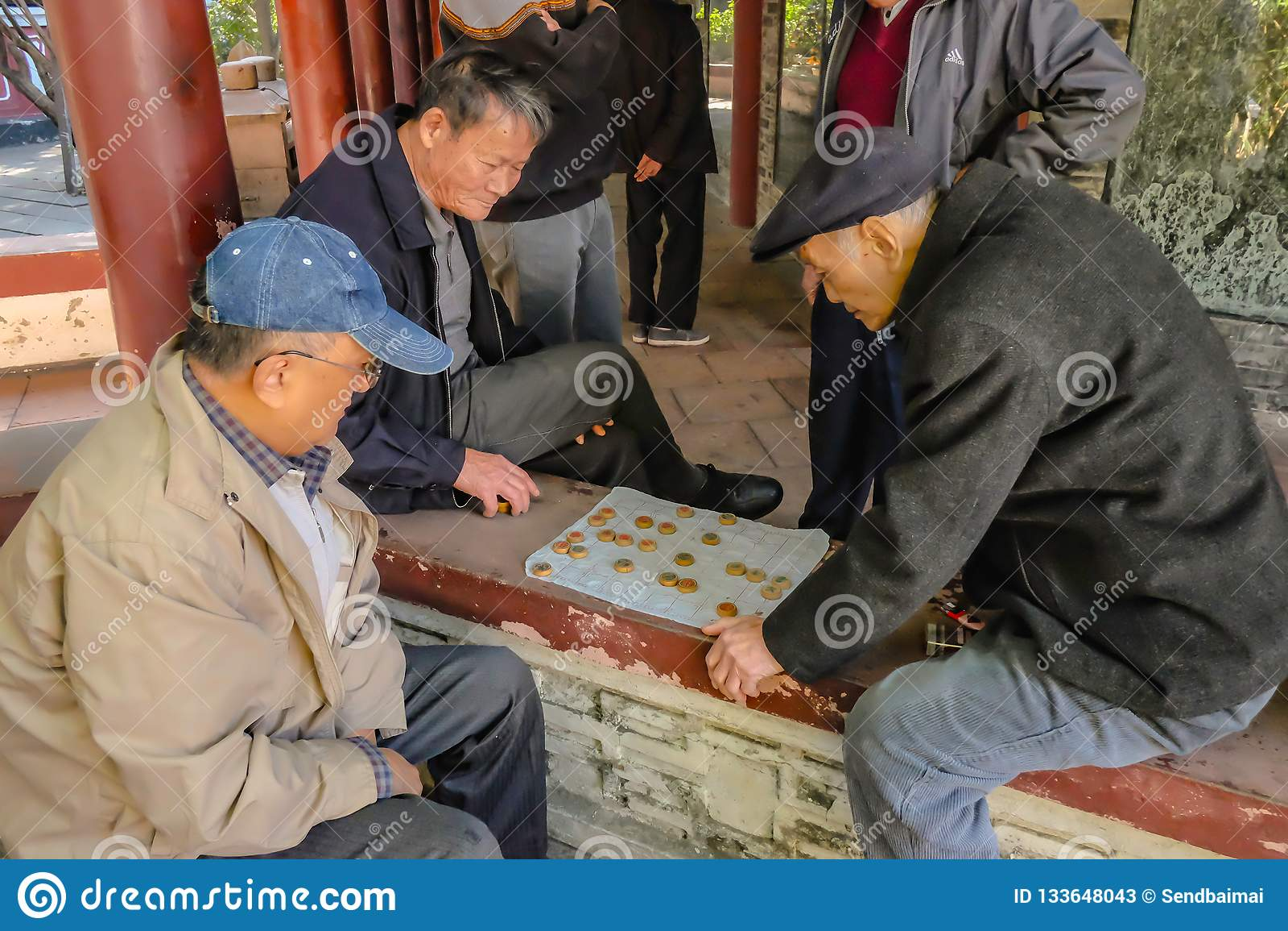 El pueblo chino mayor dejó se relaja y jugando a ajedrez chino en el parque ancestral del templo China de la ciudad de Foshan
