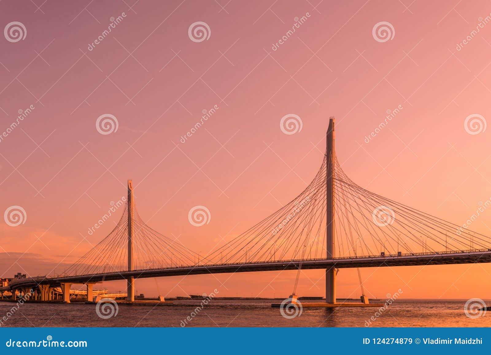 El puente del camino de la carretera del círculo sobre el río de Neva cerca de la boca de ella sobre la hora del oro durante la p