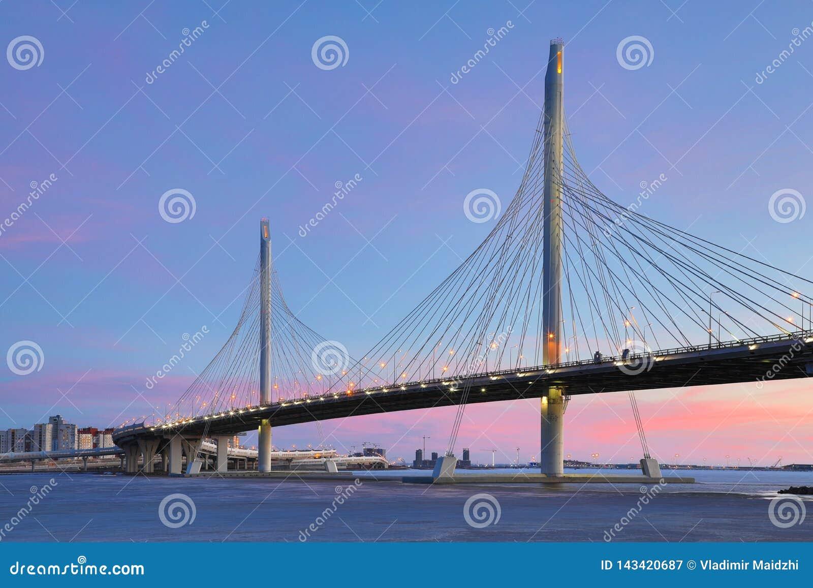 El puente del camino de la carretera del c?rculo sobre el r?o de Neva cerca de la boca de ella sobre la hora azul despu?s de la p
