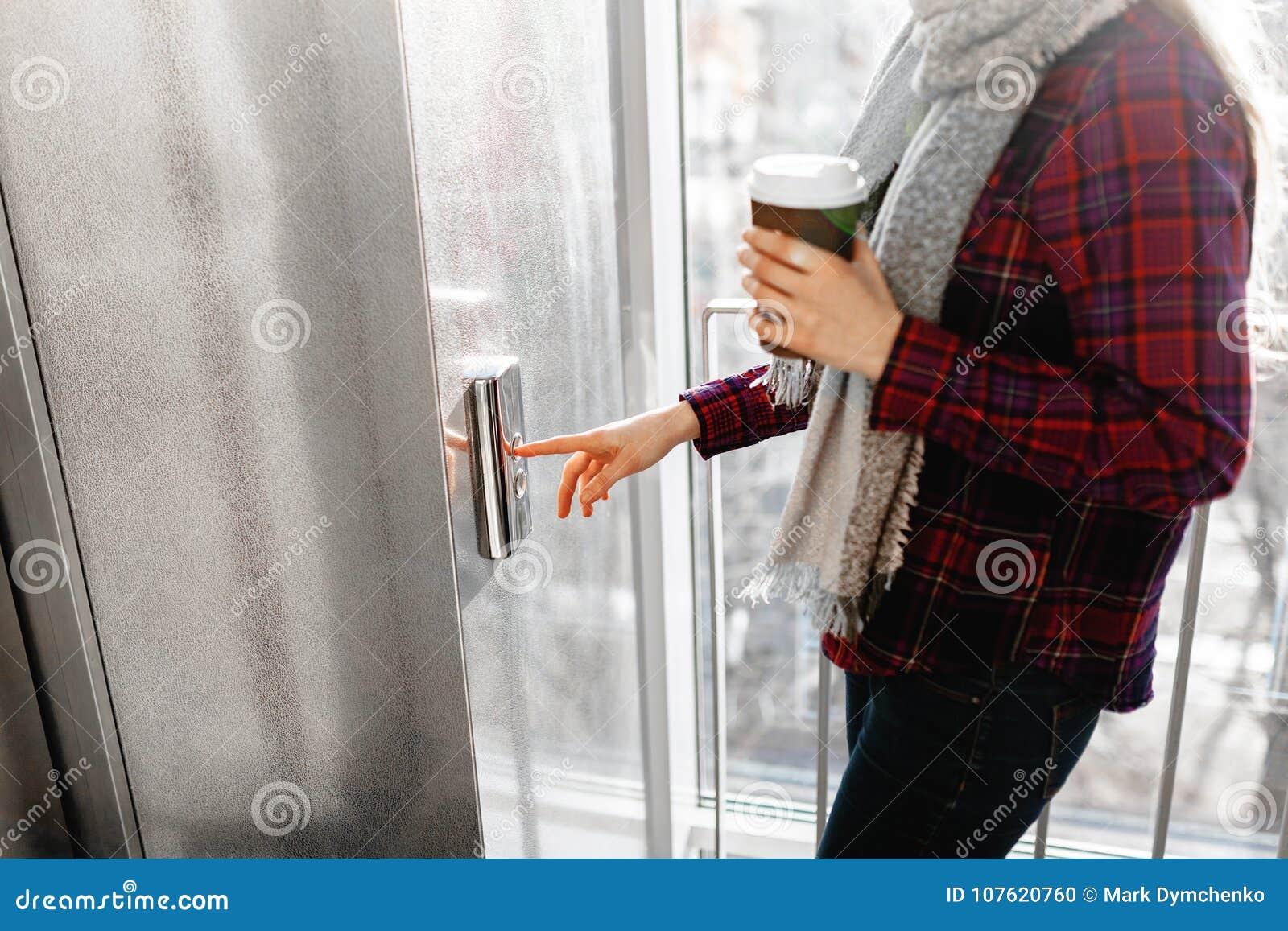 El pulgar presiona el botón del elevador, una mano que alcanza para el botón, el elevador que espera de la muchacha para, comienz