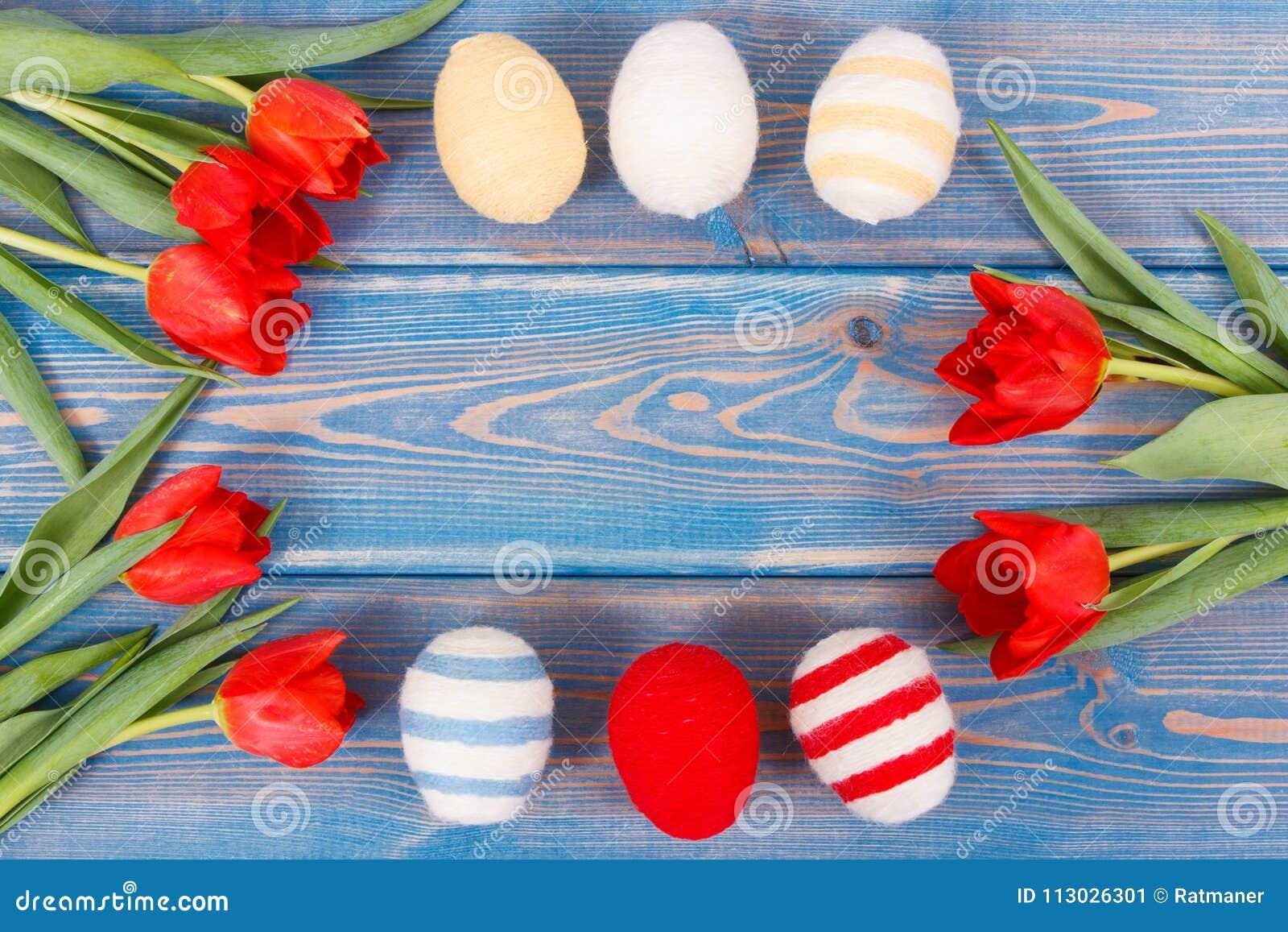 El ramo de tulipanes y de huevos de Pascua rojos envolvió la secuencia de lana, decoración festiva