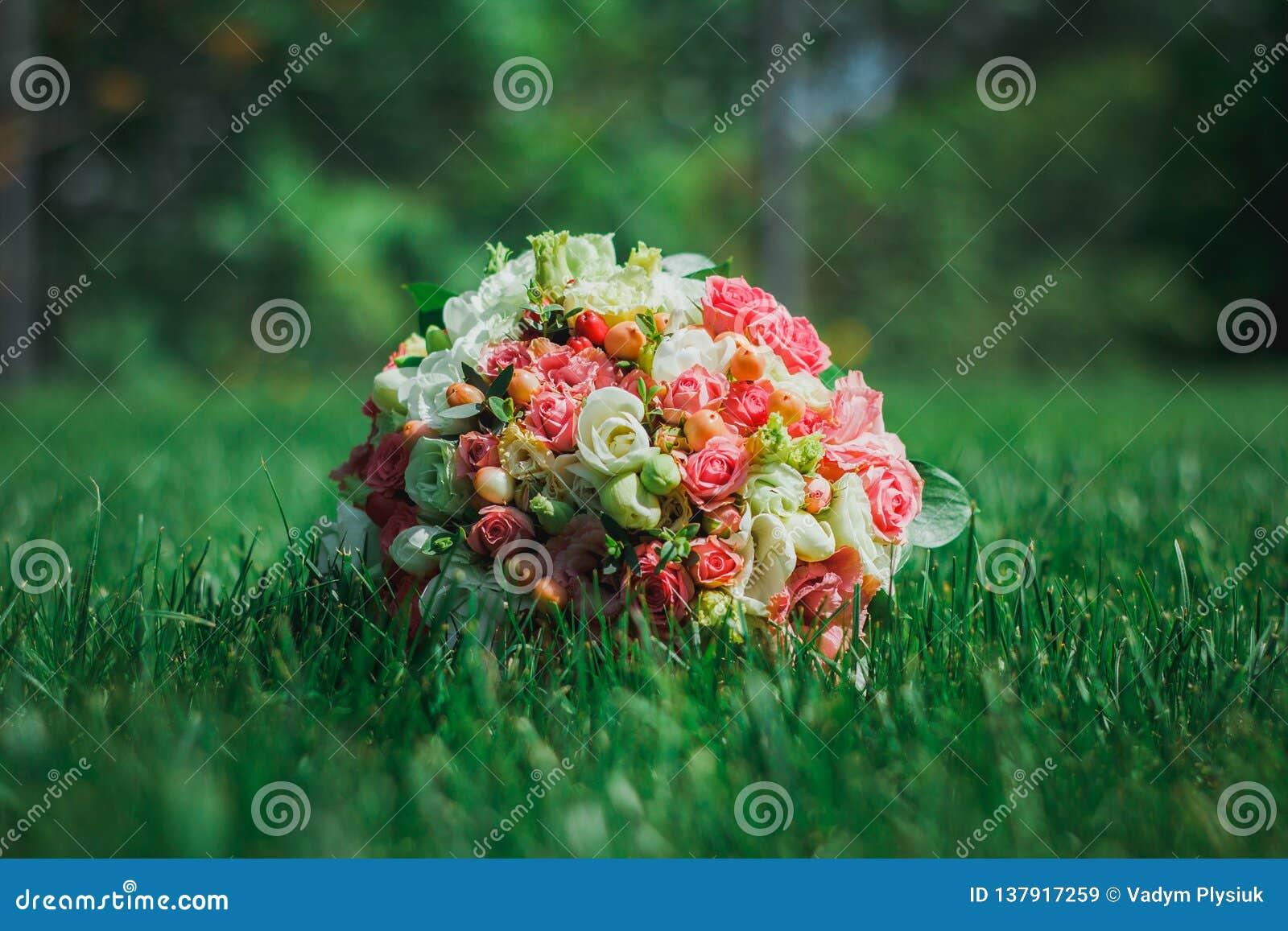 El ramo que se casa clásico de rosas, del eustoma y de la fresia miente en la hierba densa Foto verde clara y esmeralda del veran