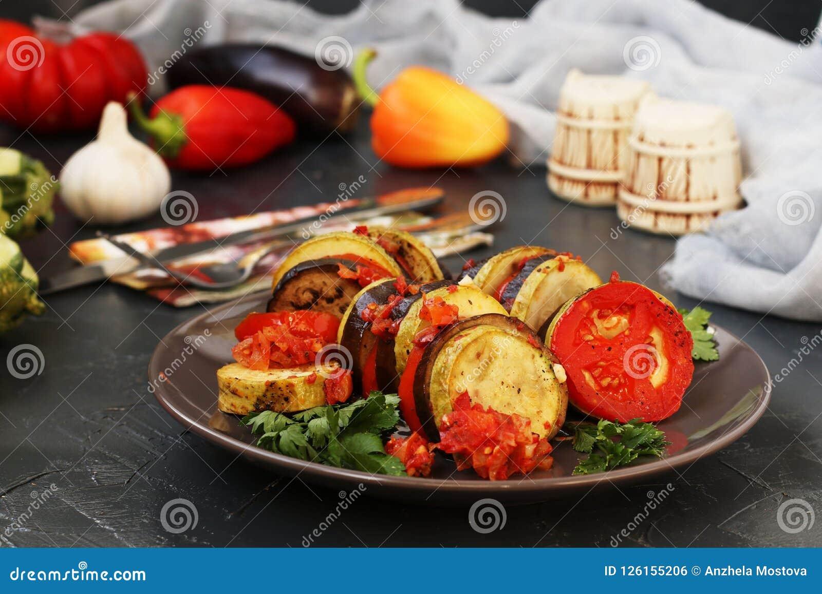 El ratatouille está situado en una placa en un fondo oscuro Verduras cocidas: berenjenas, calabacín y tomates