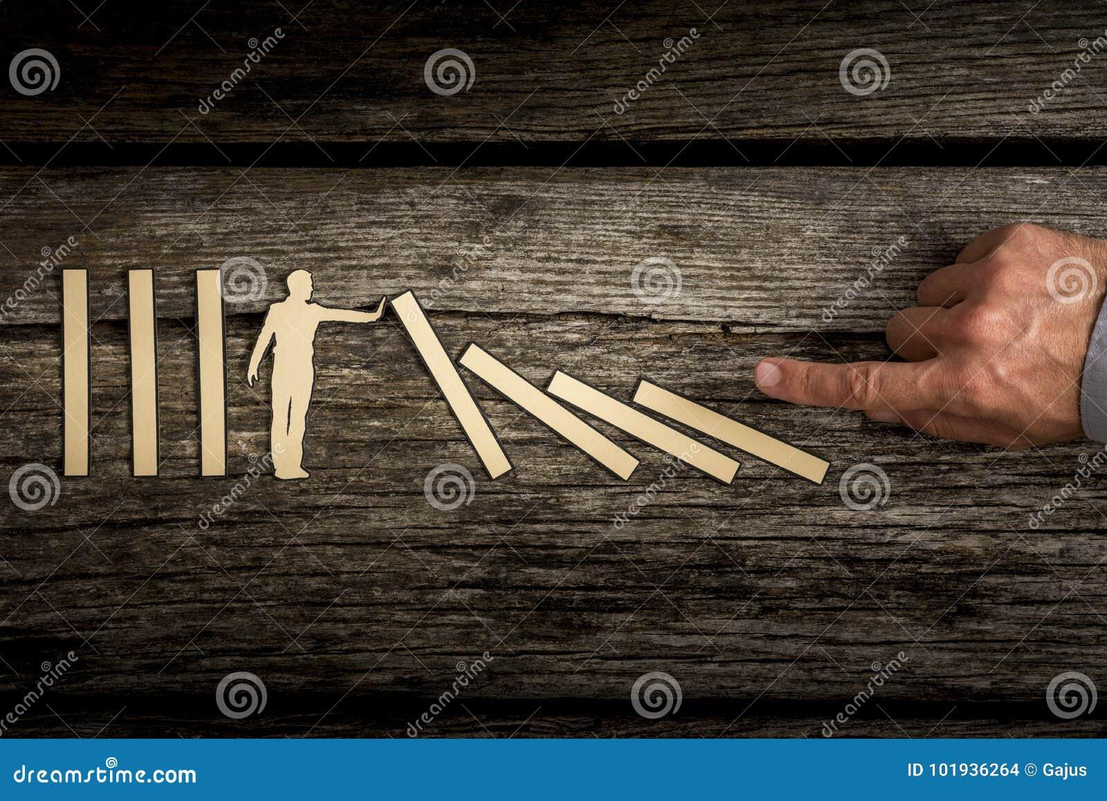 El recorte de un hombre que soporta dominós caidos como ser humano empuja manualmente
