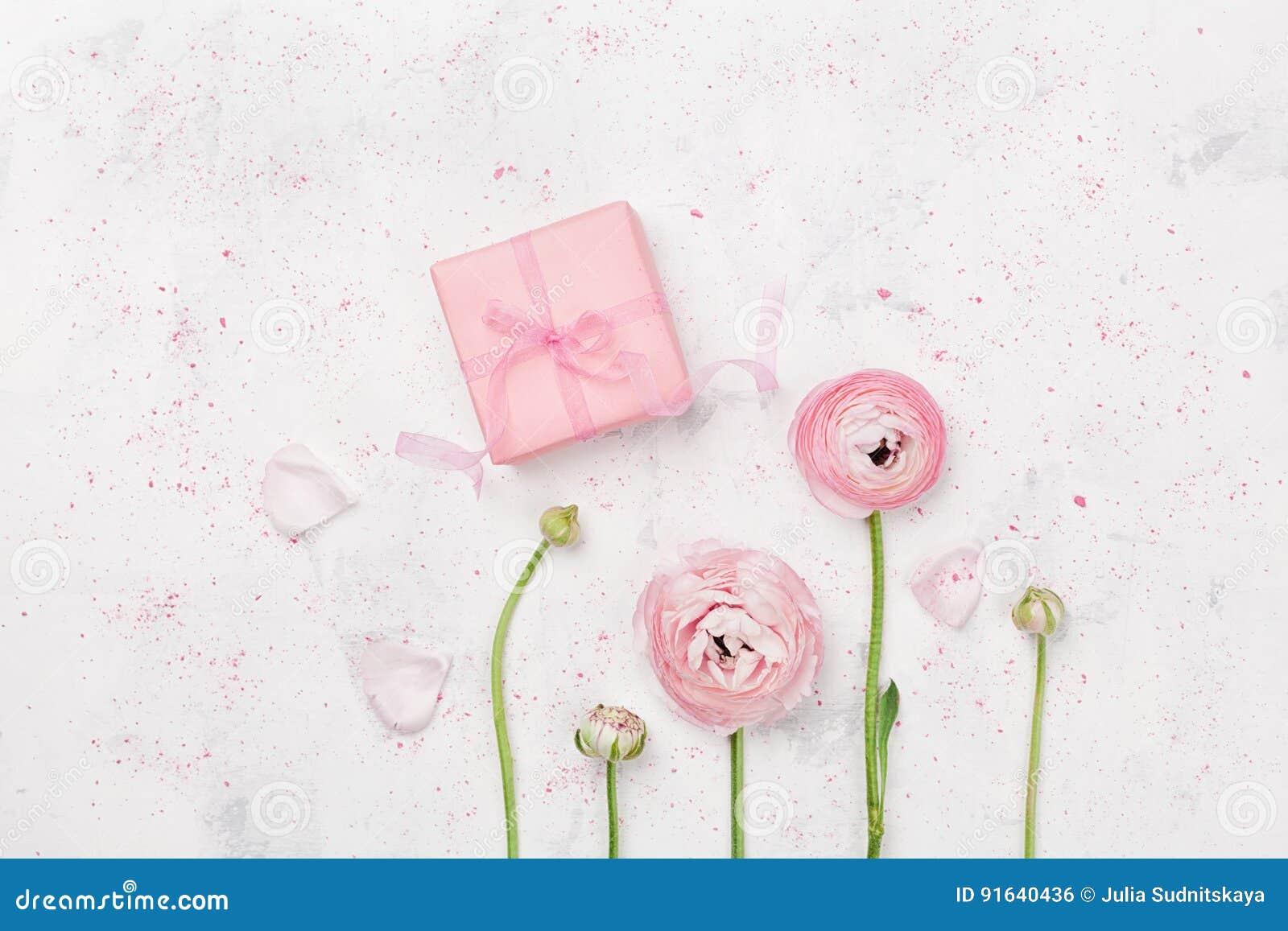 El regalo o el actual ranúnculo del caja y hermoso florecen en la tabla blanca desde arriba para casarse la maqueta o la endecha