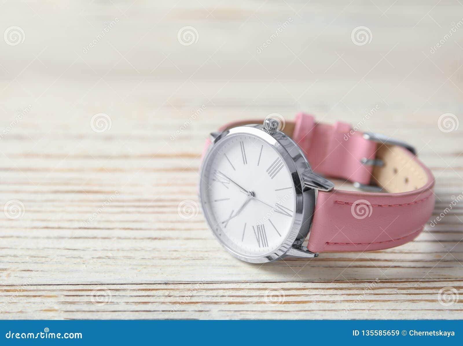 El reloj de las mujeres elegantes en la tabla de madera, espacio para el texto Moda