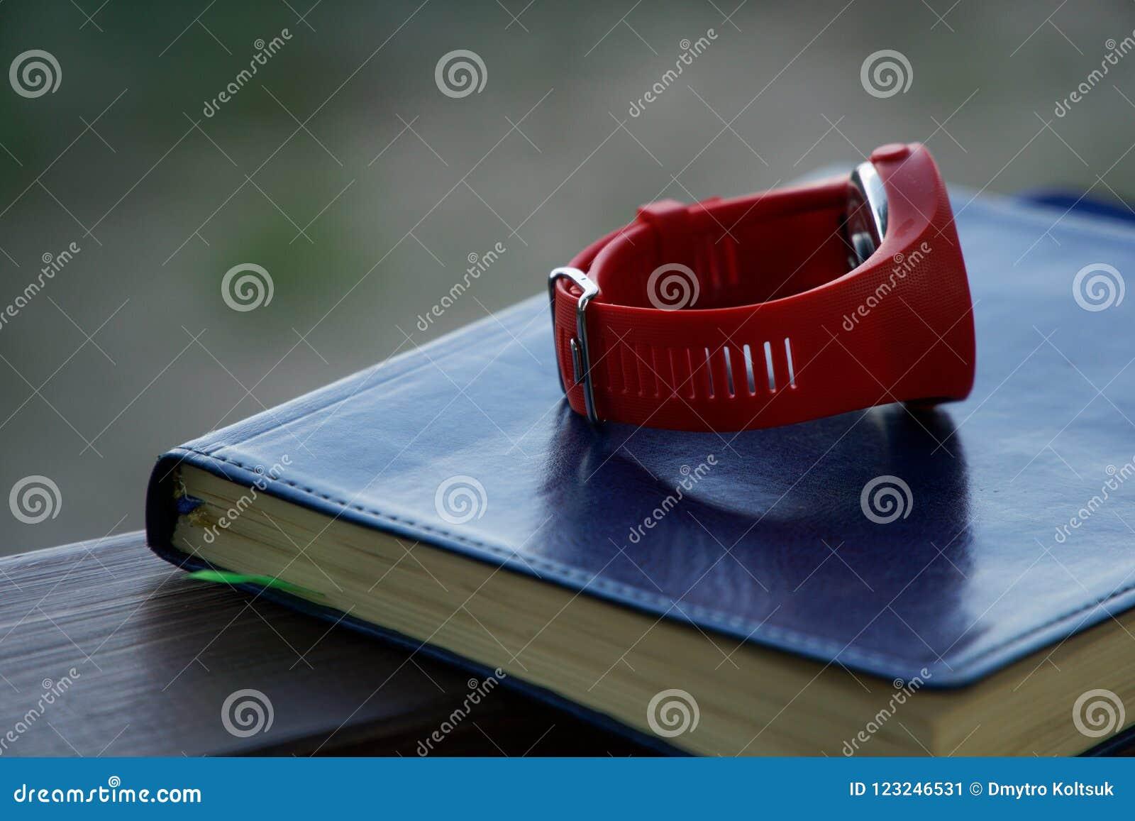 El reloj rojo del deporte en el cuaderno miente en la barandilla de madera en el parque, concepto del negocio