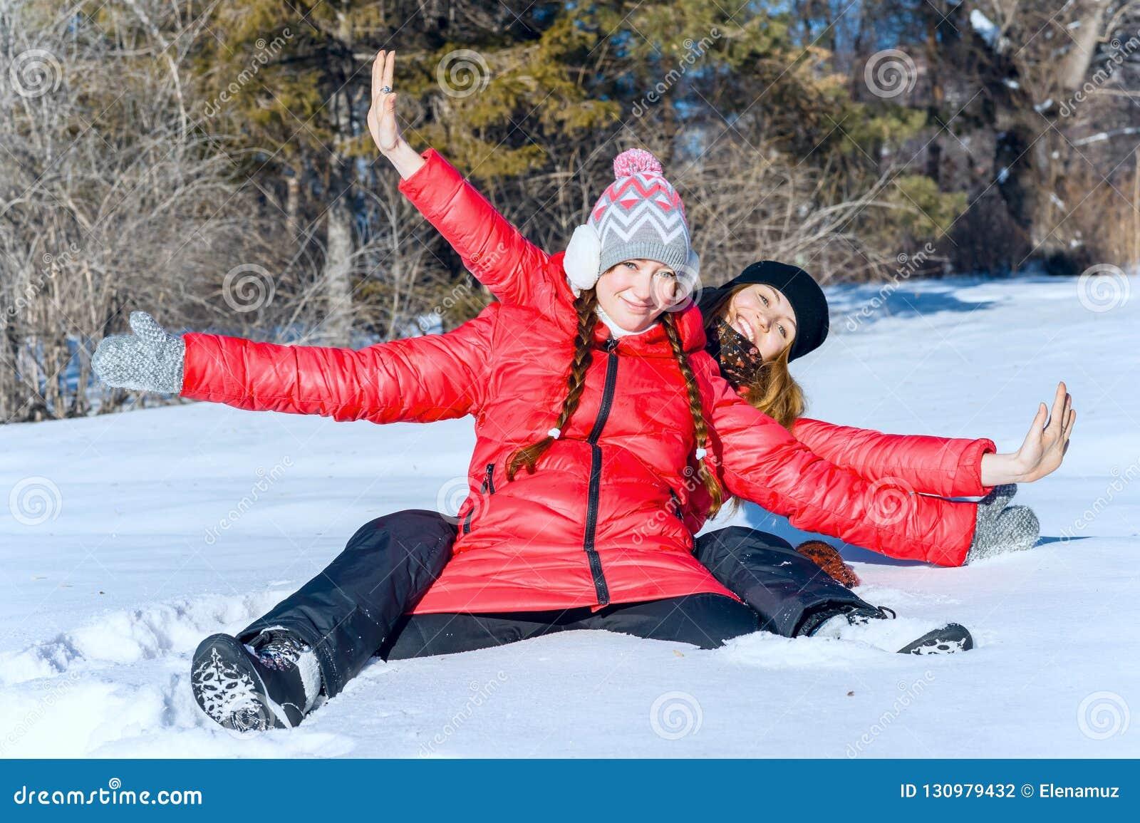 El retrato al aire libre de dos muchachas se divierte y goza de la nieve fresca en un día de invierno hermoso en parque del invie