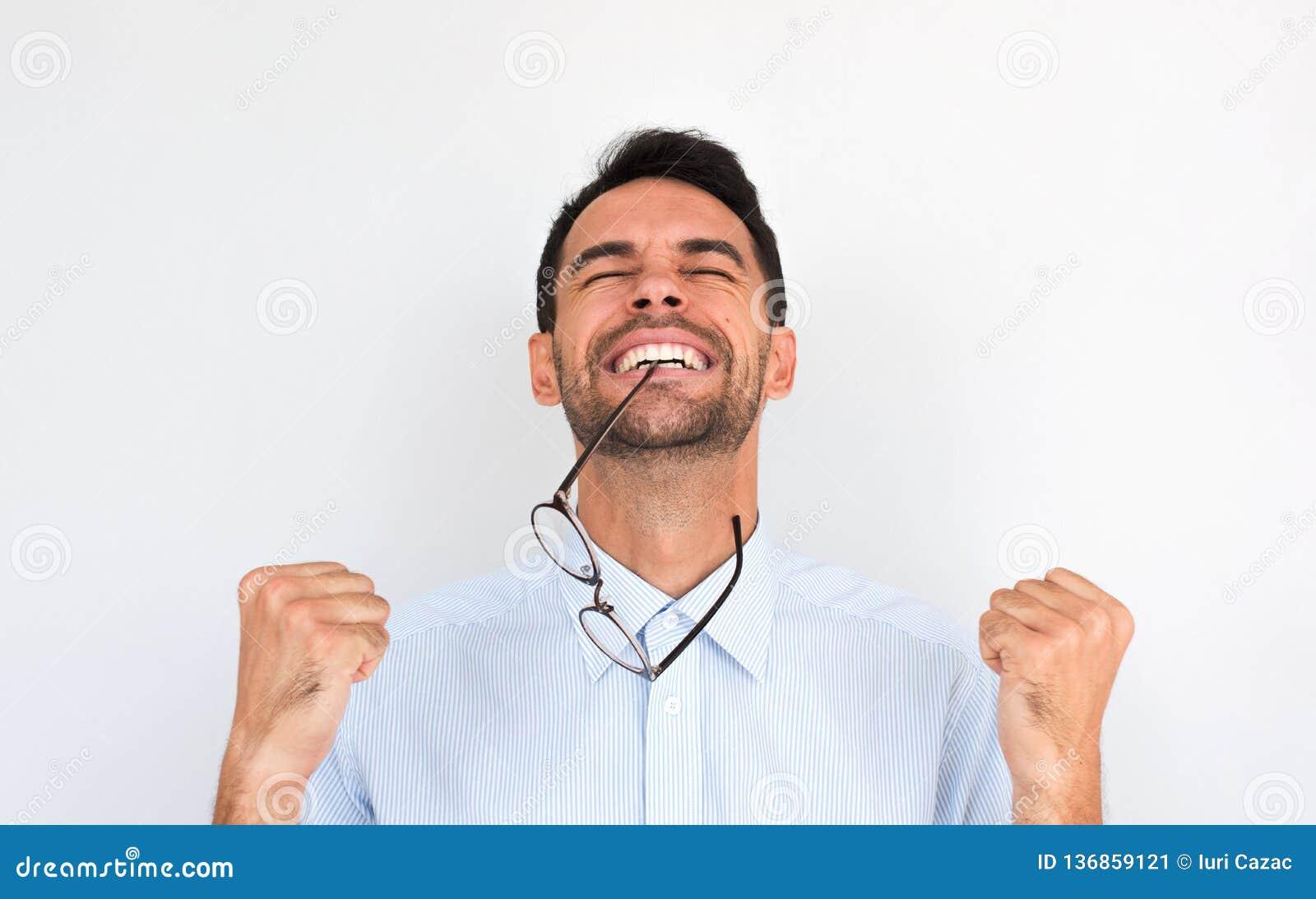 El retrato de Horziontal del varón joven del ganador sin afeitar feliz aprieta los puños y celebra su victoria, con las gafas en