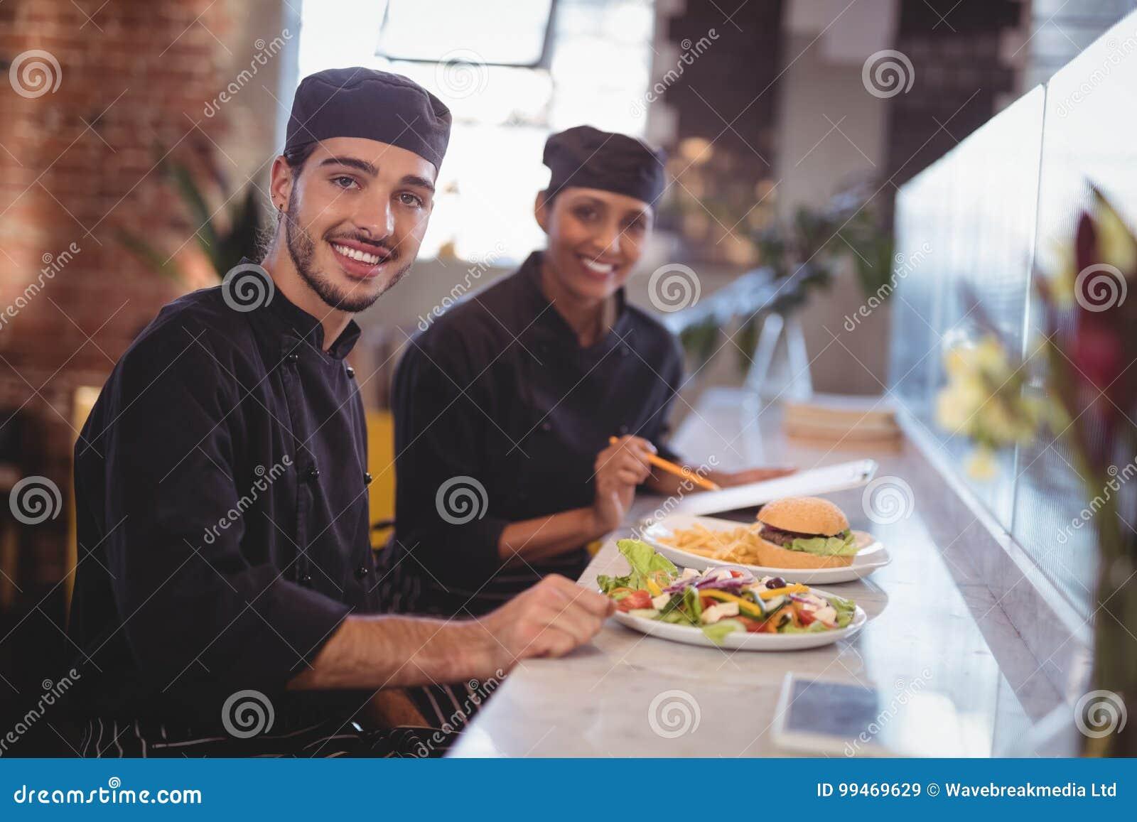 El retrato de jóvenes sonrientes espera al personal que se sienta con la comida y el tablero en el contador