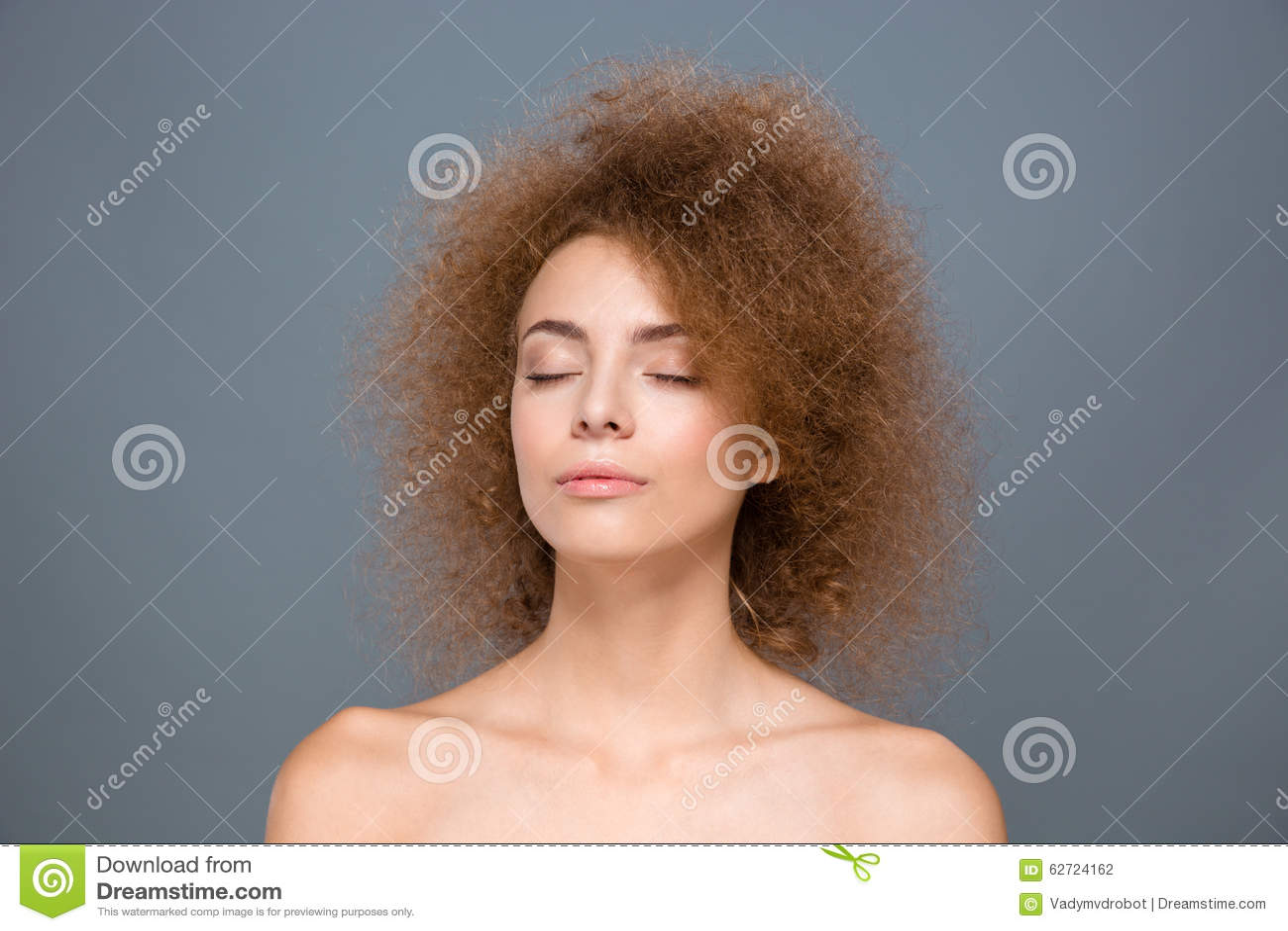 El retrato de la belleza de la mujer joven relajada rizada con los ojos se cerró