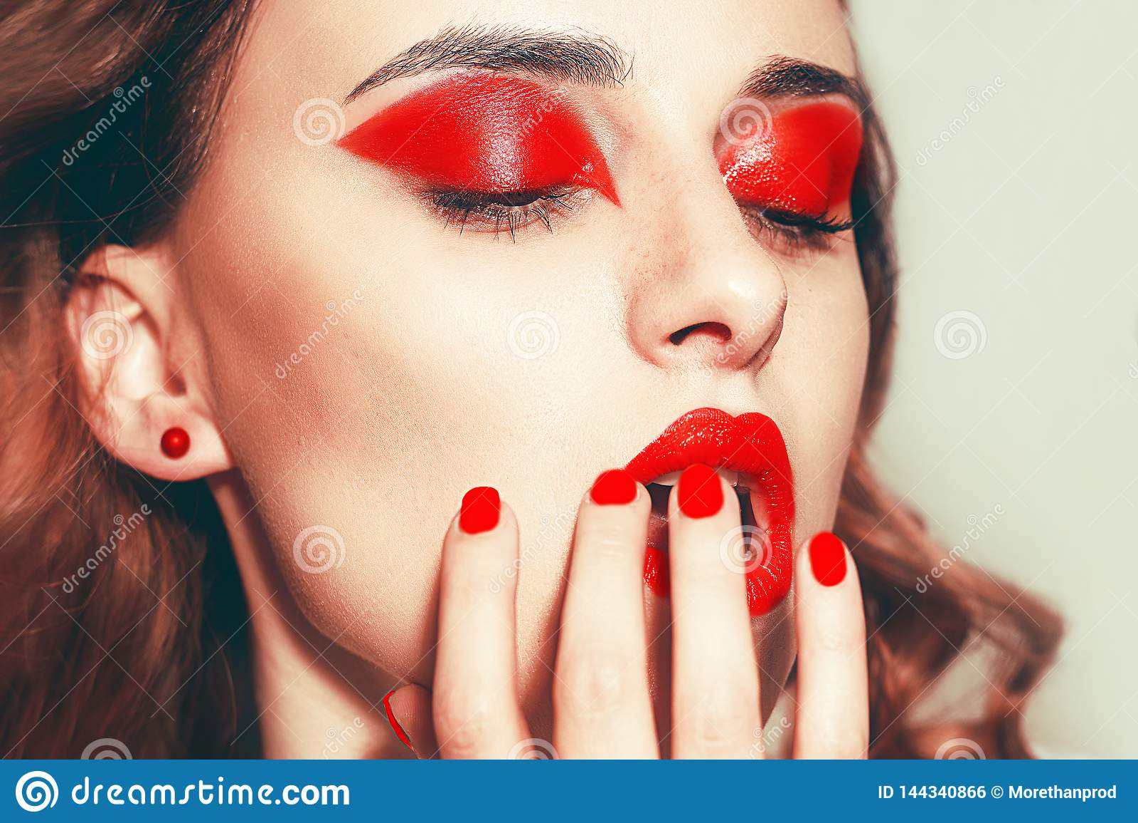 El retrato de la belleza de mujeres atractivas con encanto compone Labios rojos y sombreadores de ojos rojos, neils Cara del mode