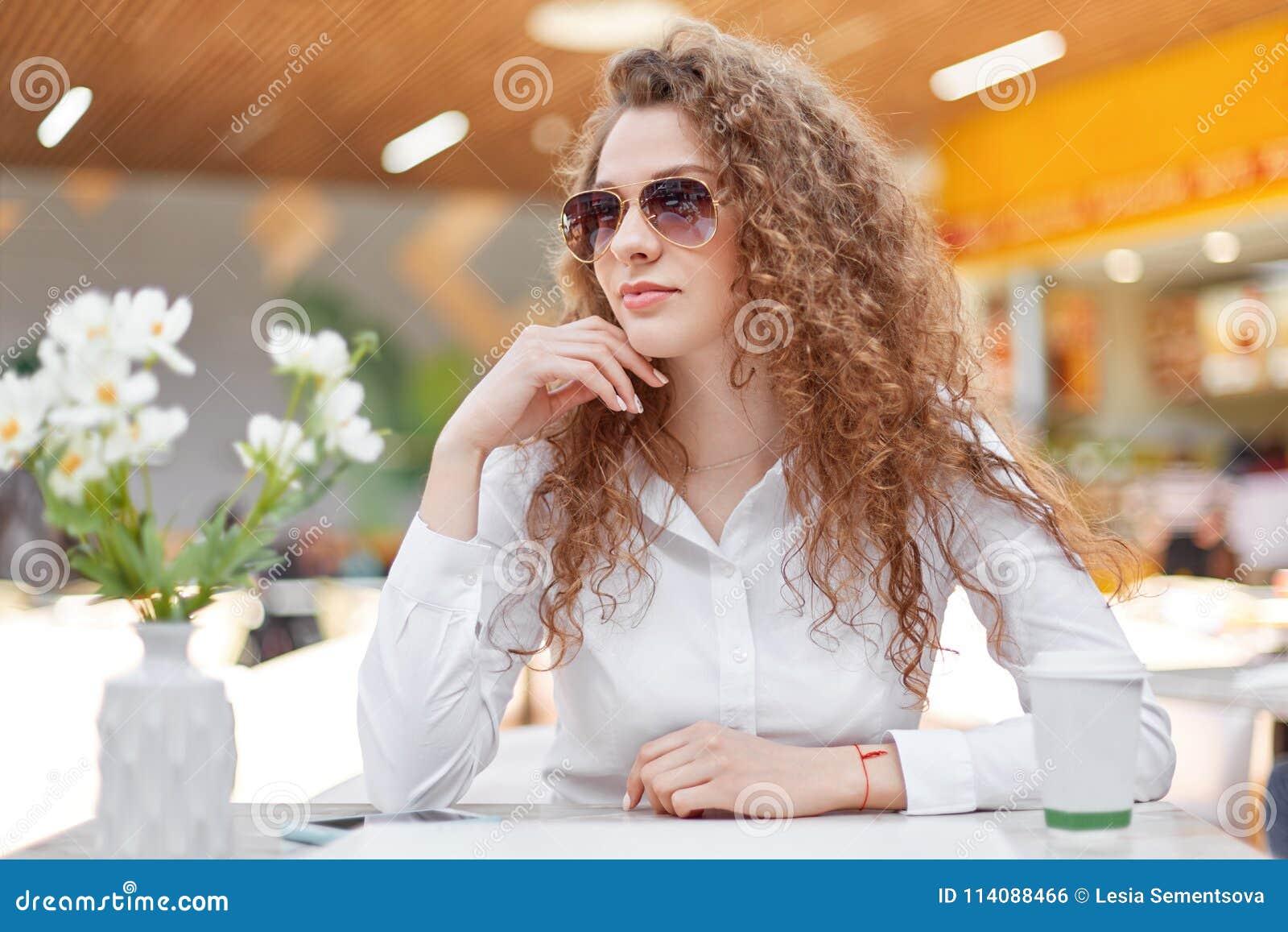 acf486ff6d El retrato de la empresaria pensativa lleva la blusa elegante y las gafas  de sol, miran lejos, se sientan en cafetería como las esperas para el socio  ...