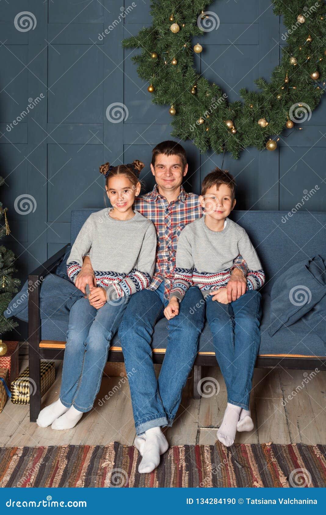 El retrato de la familia, papá con dos niños se está sentando en el sofá que sonríen en el cuarto adornado del Año Nuevo
