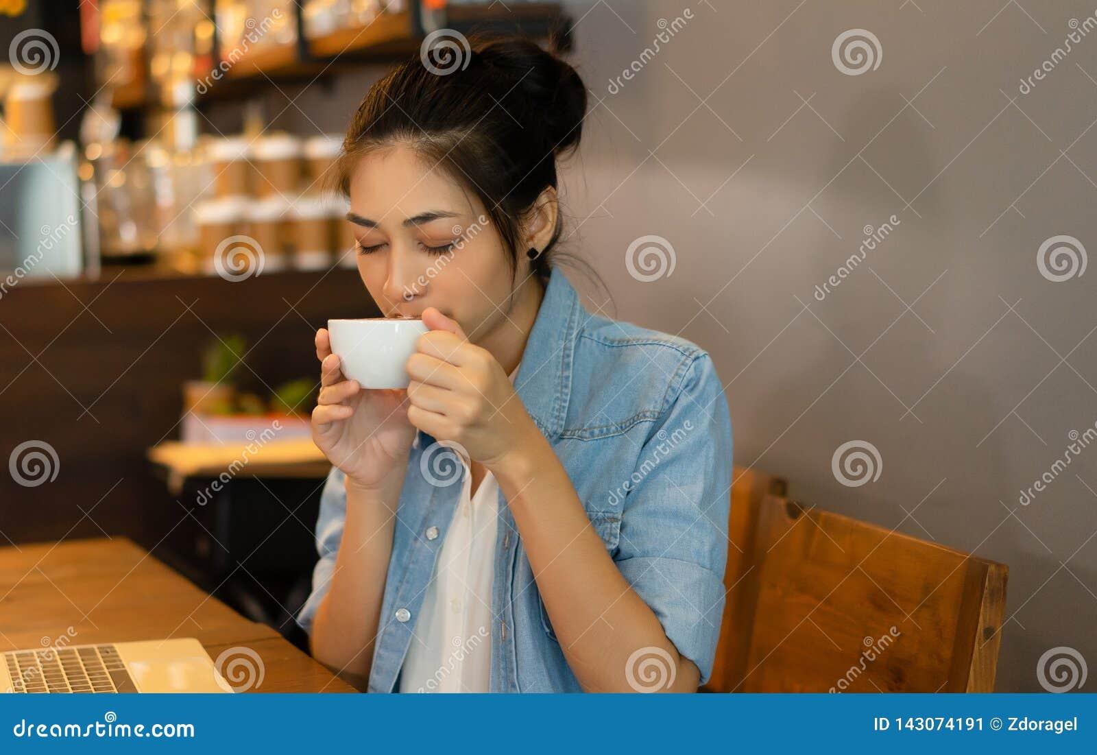 El retrato de la hembra magnífica asiática joven con sus ojos cerró el goce del olor del café delicioso fresco en la cafetería