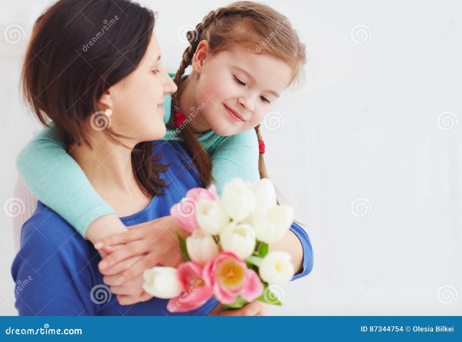 El retrato de la madre feliz y la hija con la primavera florecen el ramo