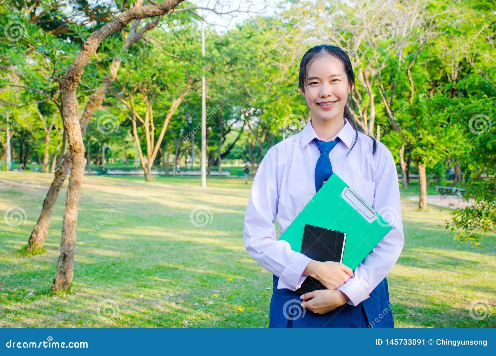 El retrato de la muchacha hermosa adolescente de la escuela secundaria del uniforme tailandés del estudiante feliz y relajarse ce