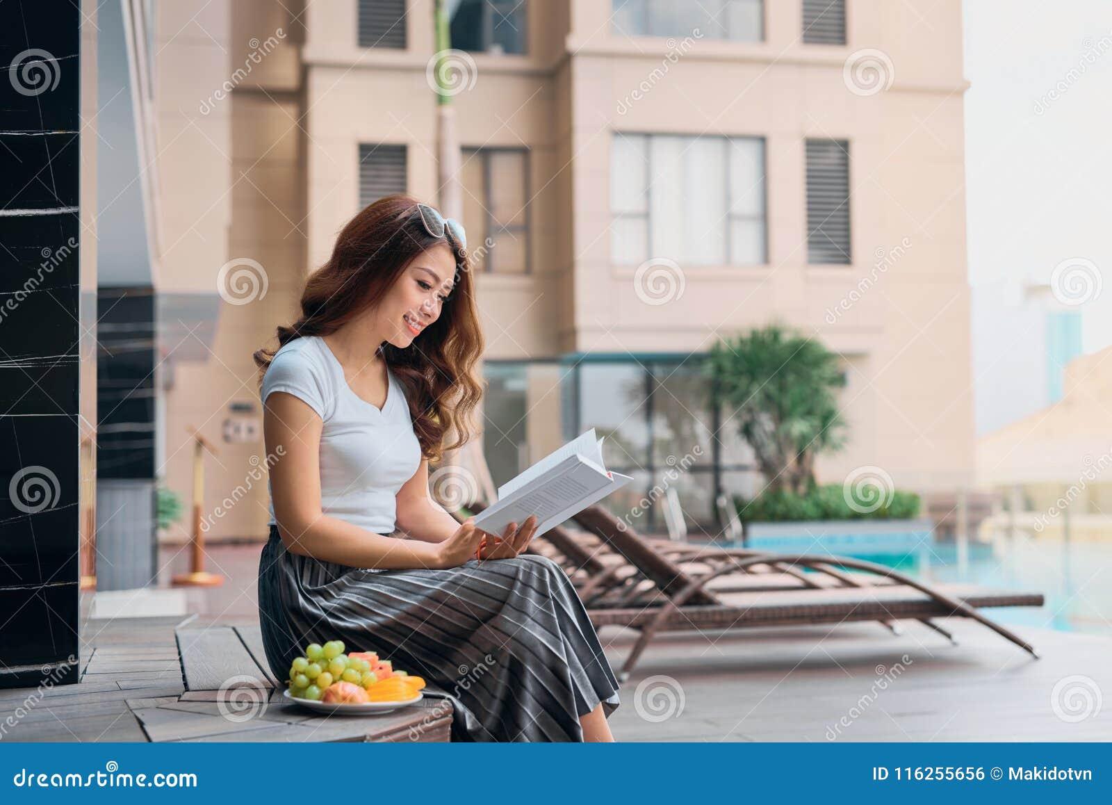 El retrato de la mujer bastante alegre se relaja y del libro de lectura en vaca