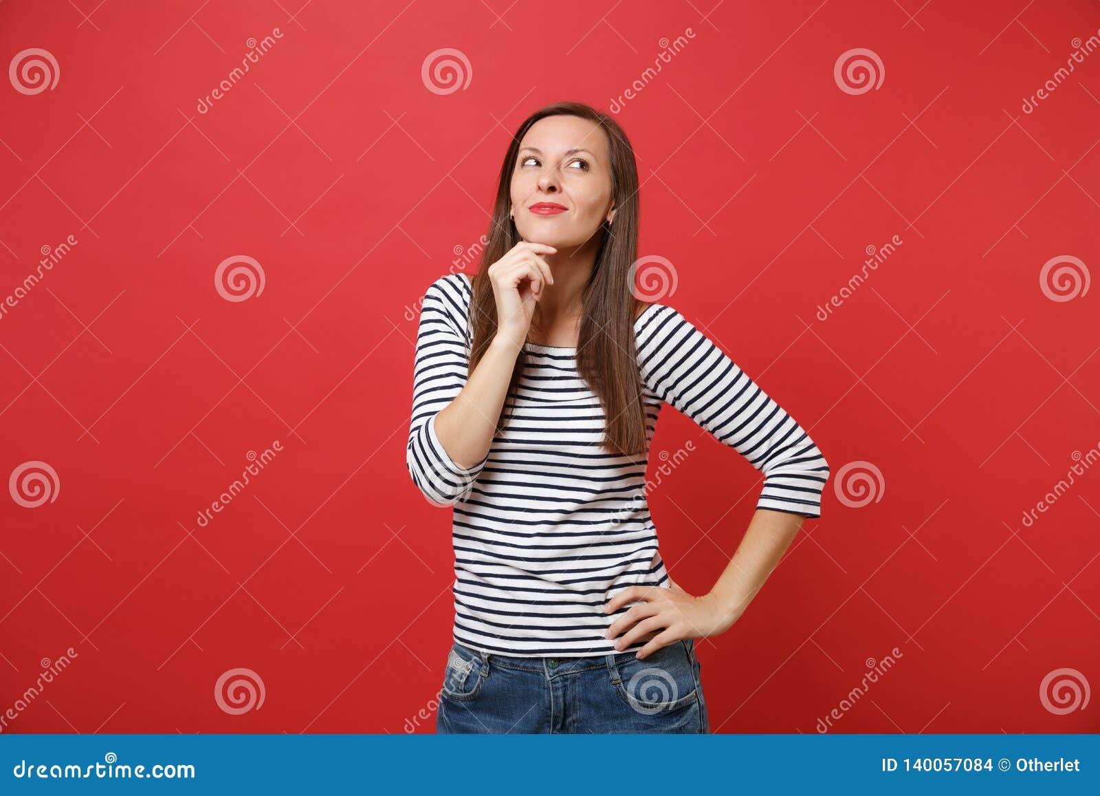 El retrato de la mujer joven sonriente soñadora en la ropa rayada que miraba para arriba, puso la mano apoya para arriba en la ba