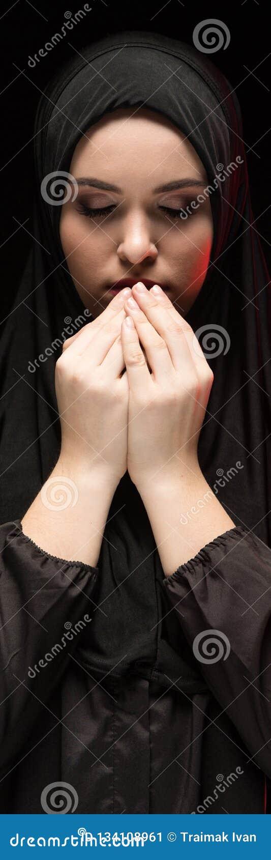El retrato de la mujer musulmán joven seria hermosa que lleva el hijab negro con las manos acerca a su cara como concepto de roga