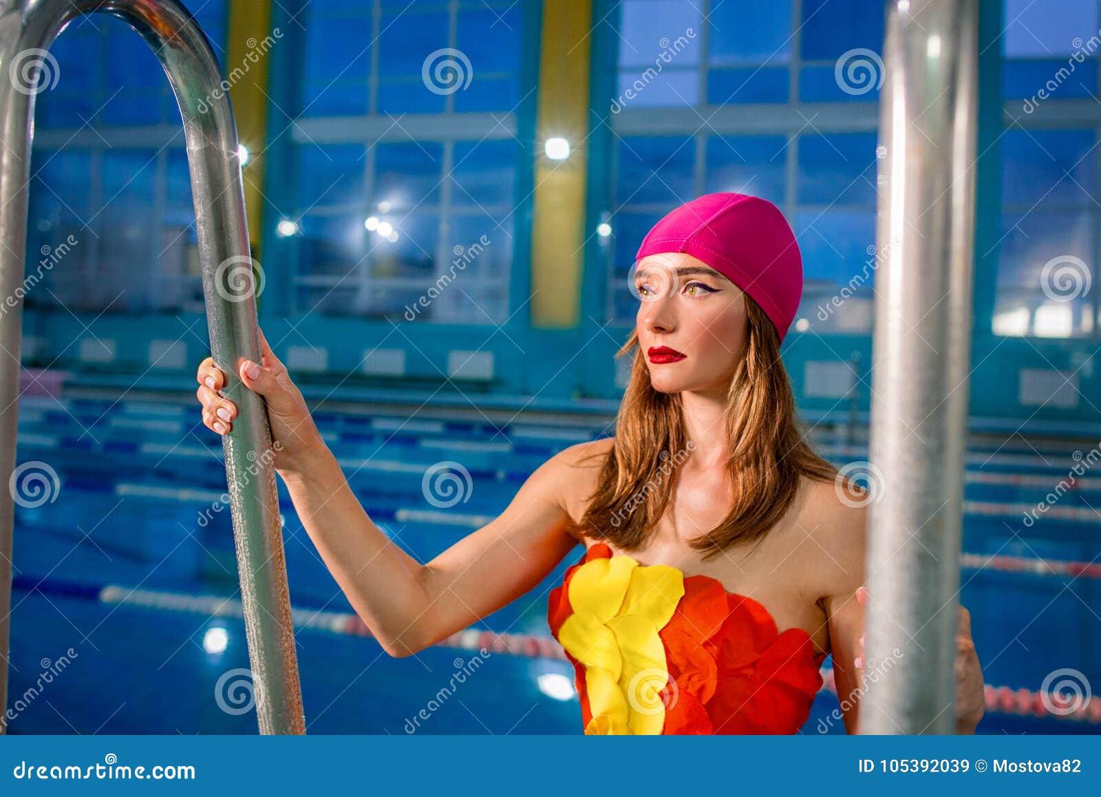 El retrato de la mujer rubia atractiva hermosa atlética con elegante compone en casquillo y bañador rosados de la nadada