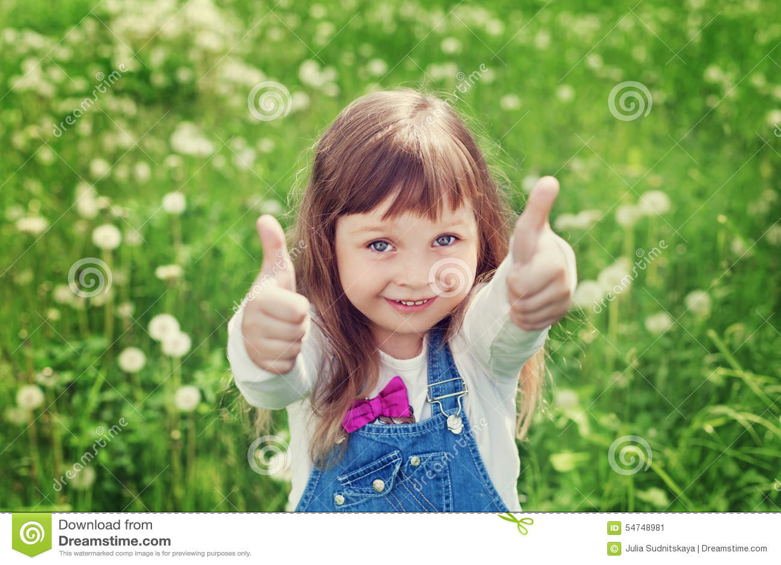 El retrato de la niña linda con los pulgares para arriba muestra una clase en el prado de la flor, concepto feliz de la niñez, ni