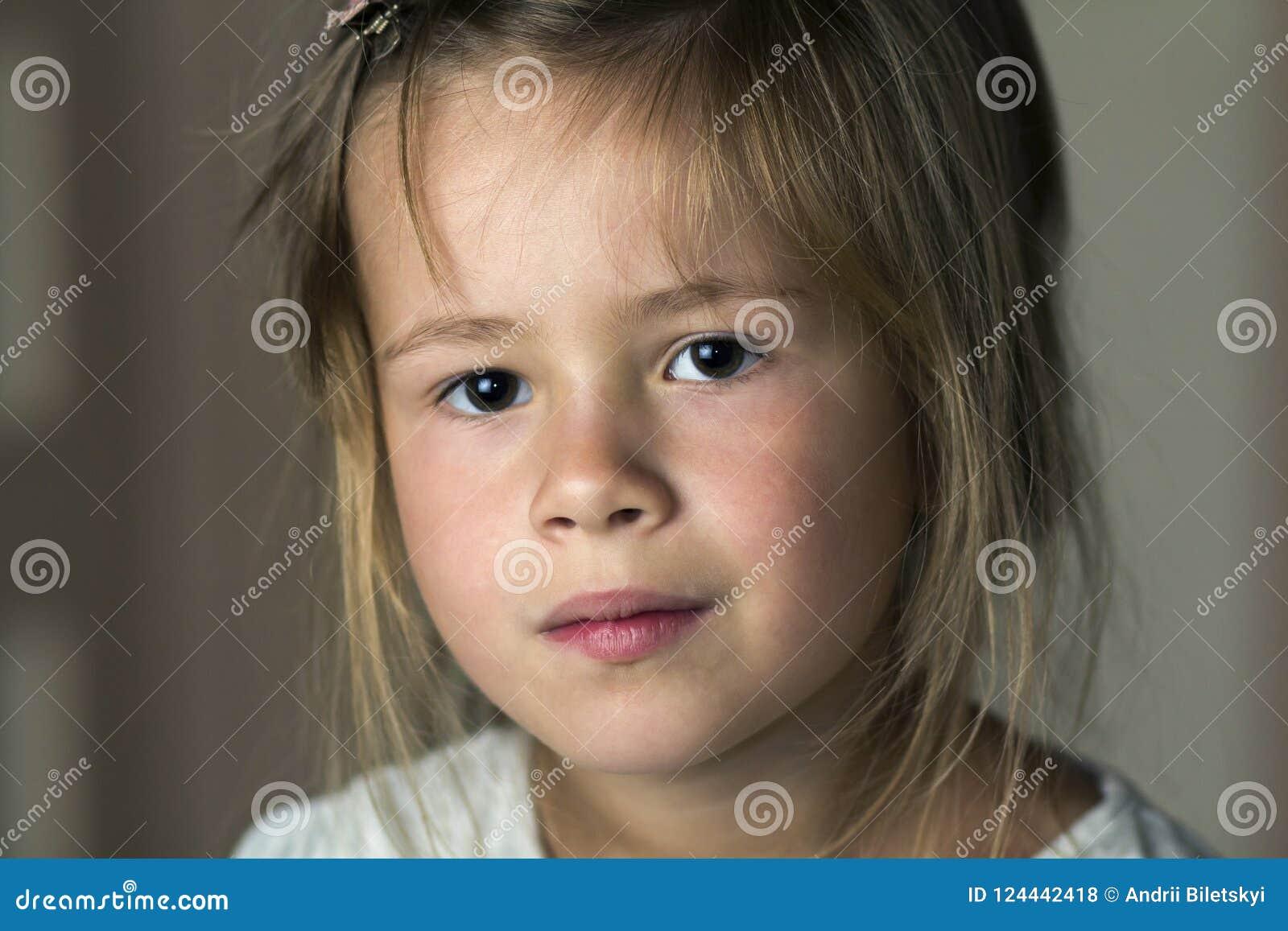 El retrato de poco muchacha linda del niño bastante joven con gris observa a
